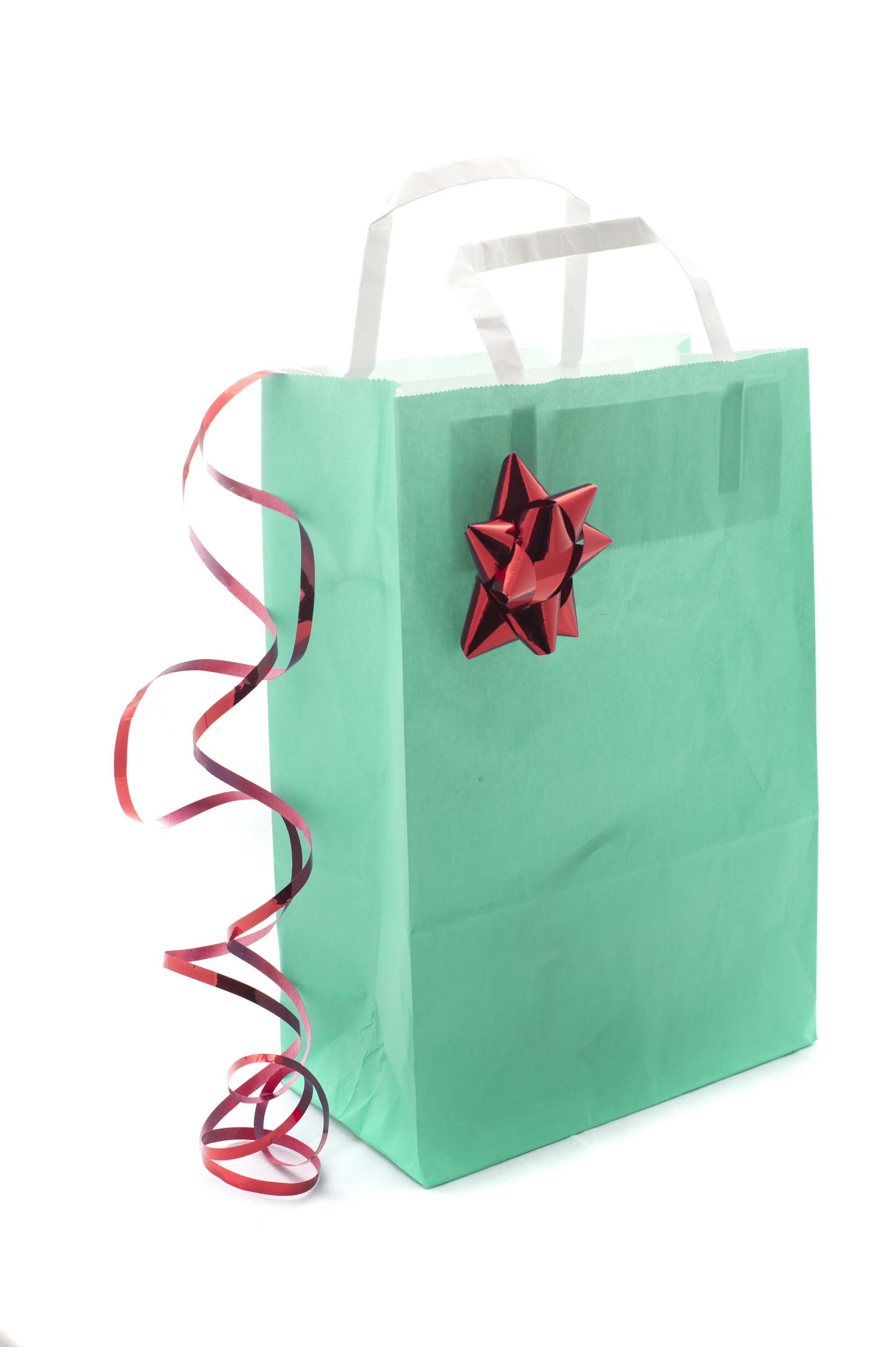 Pretty blue Christmas shopping bag decorated with a shiny metallic red bow and coiled ribbon with a blank side with copyspace for your message or advertisement, on white