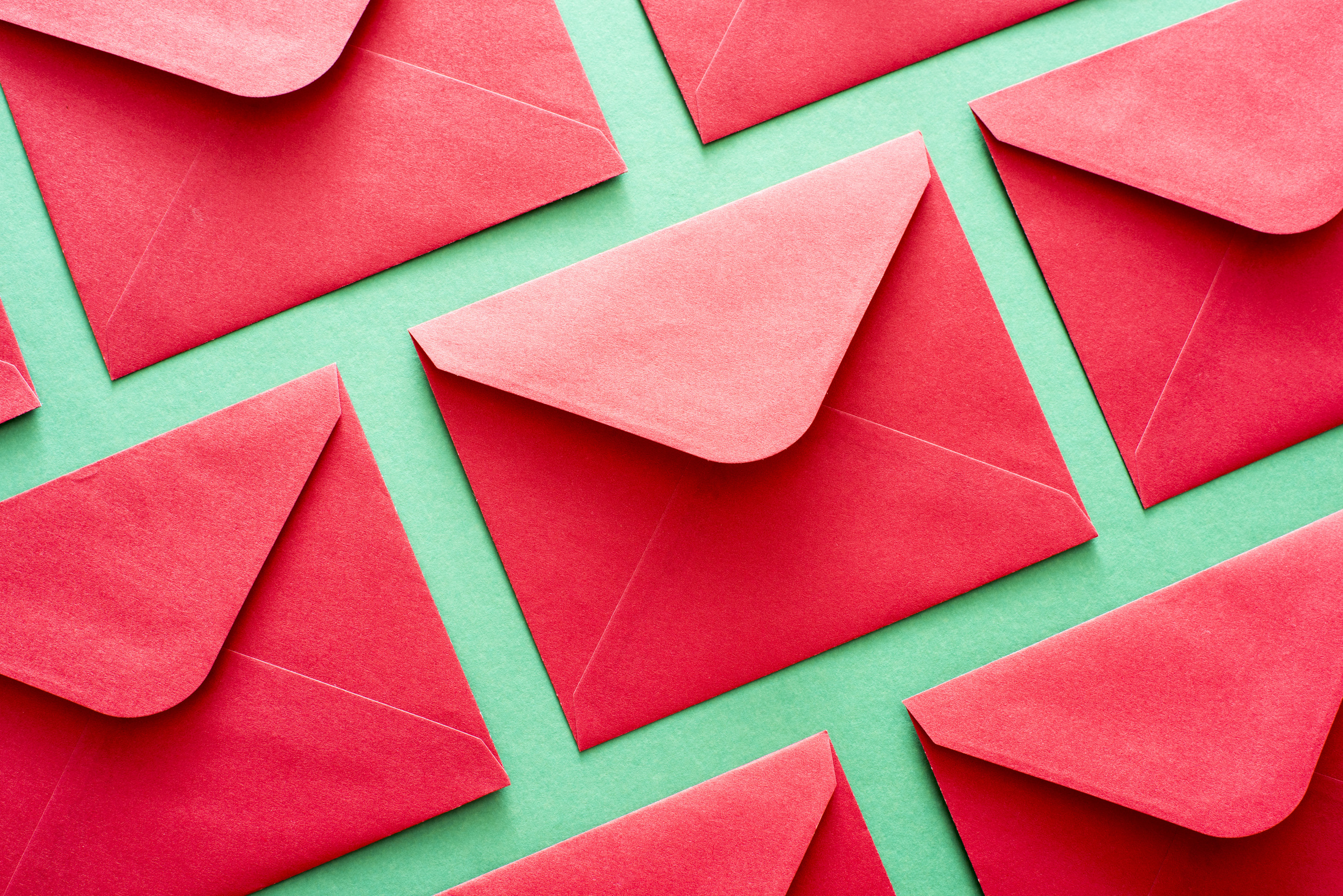 Background pattern of festive red envelopes arranged neatly in rows on a green background for your seasonal Christmas or New Year message