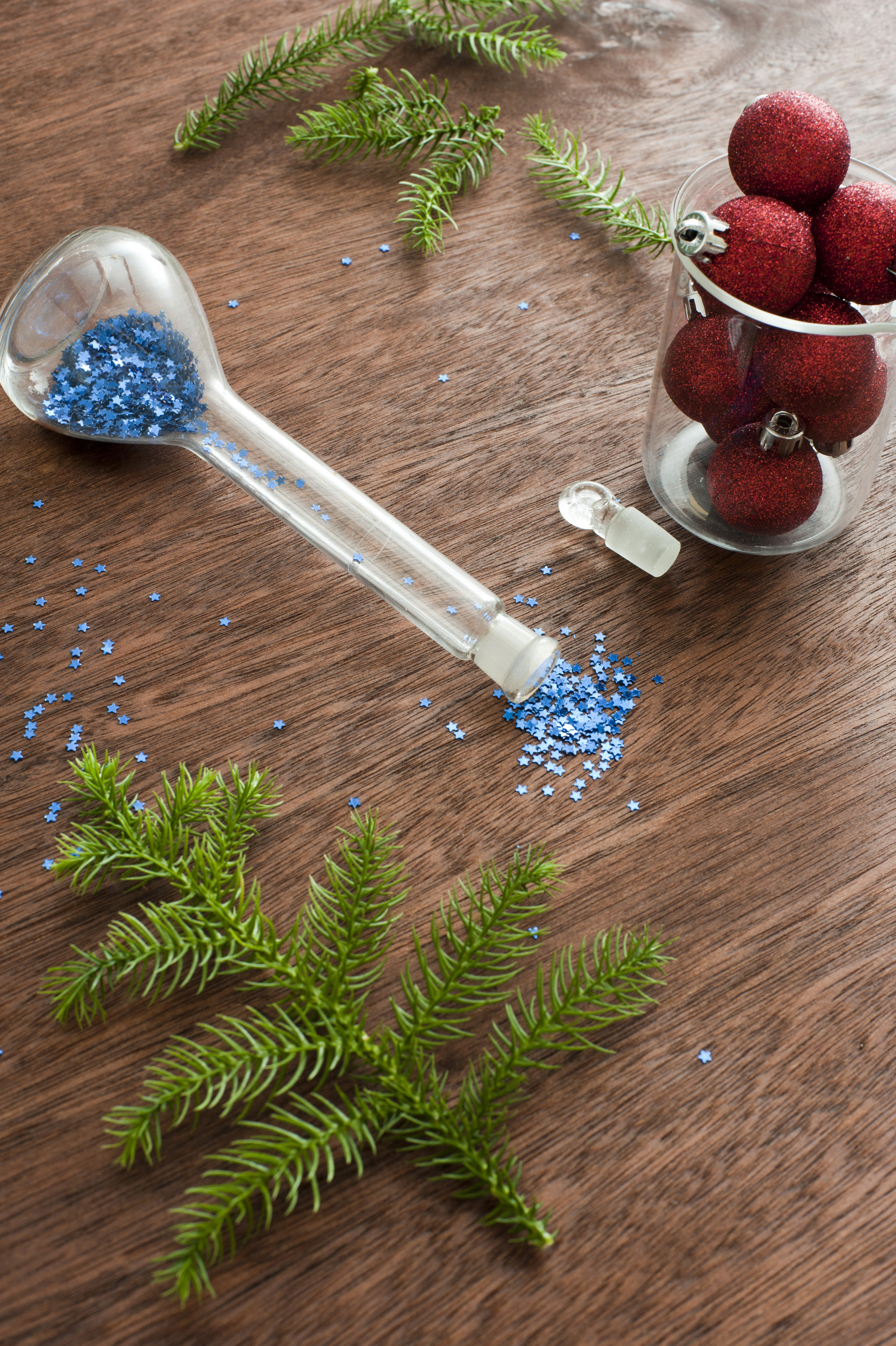Red Christmas balls, fir tree branch and scattered blue sparkles on wooden table
