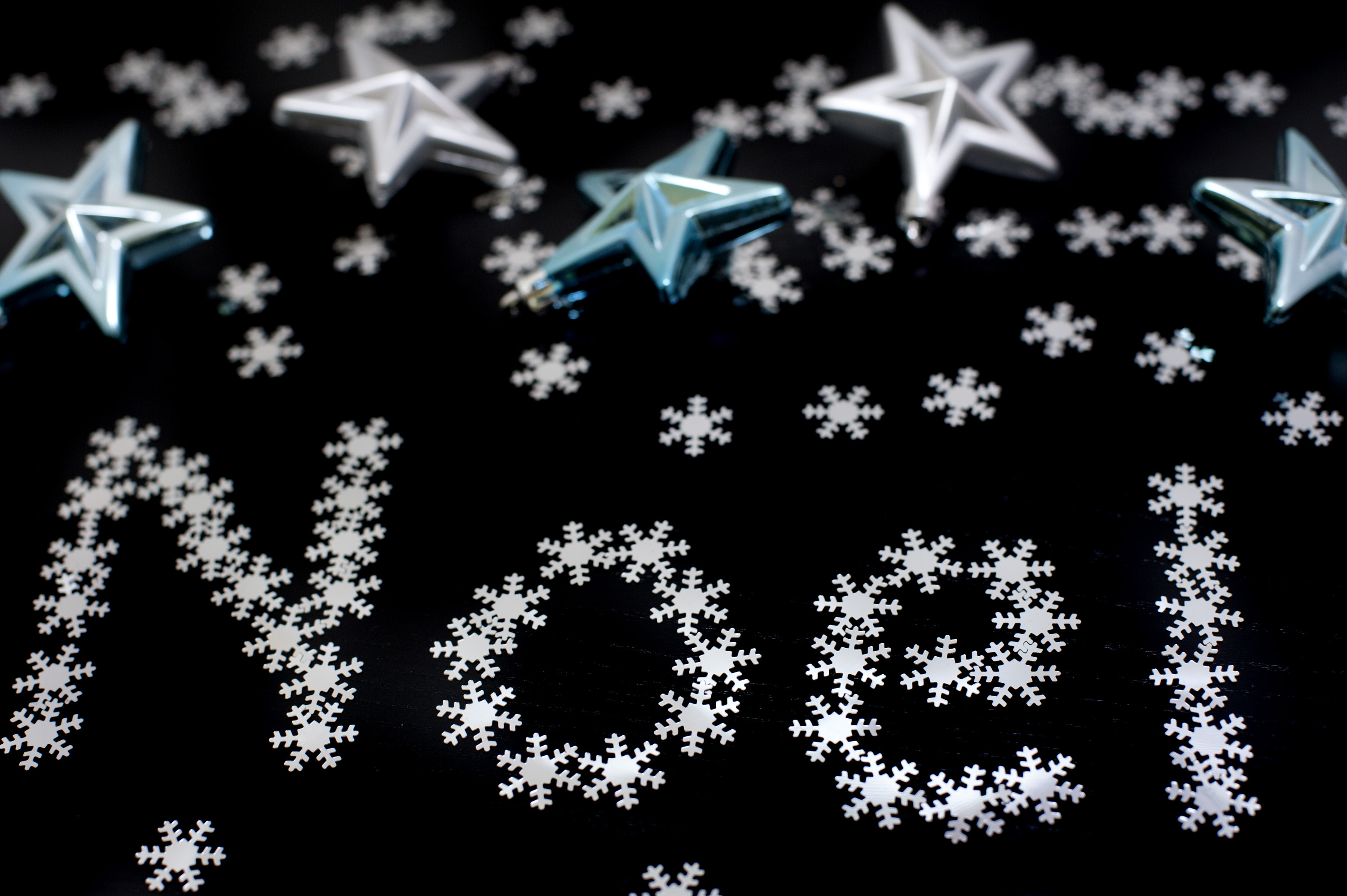 Noel greetings message with letters formed of tiny snowflakes on a dark background with Christmas stars