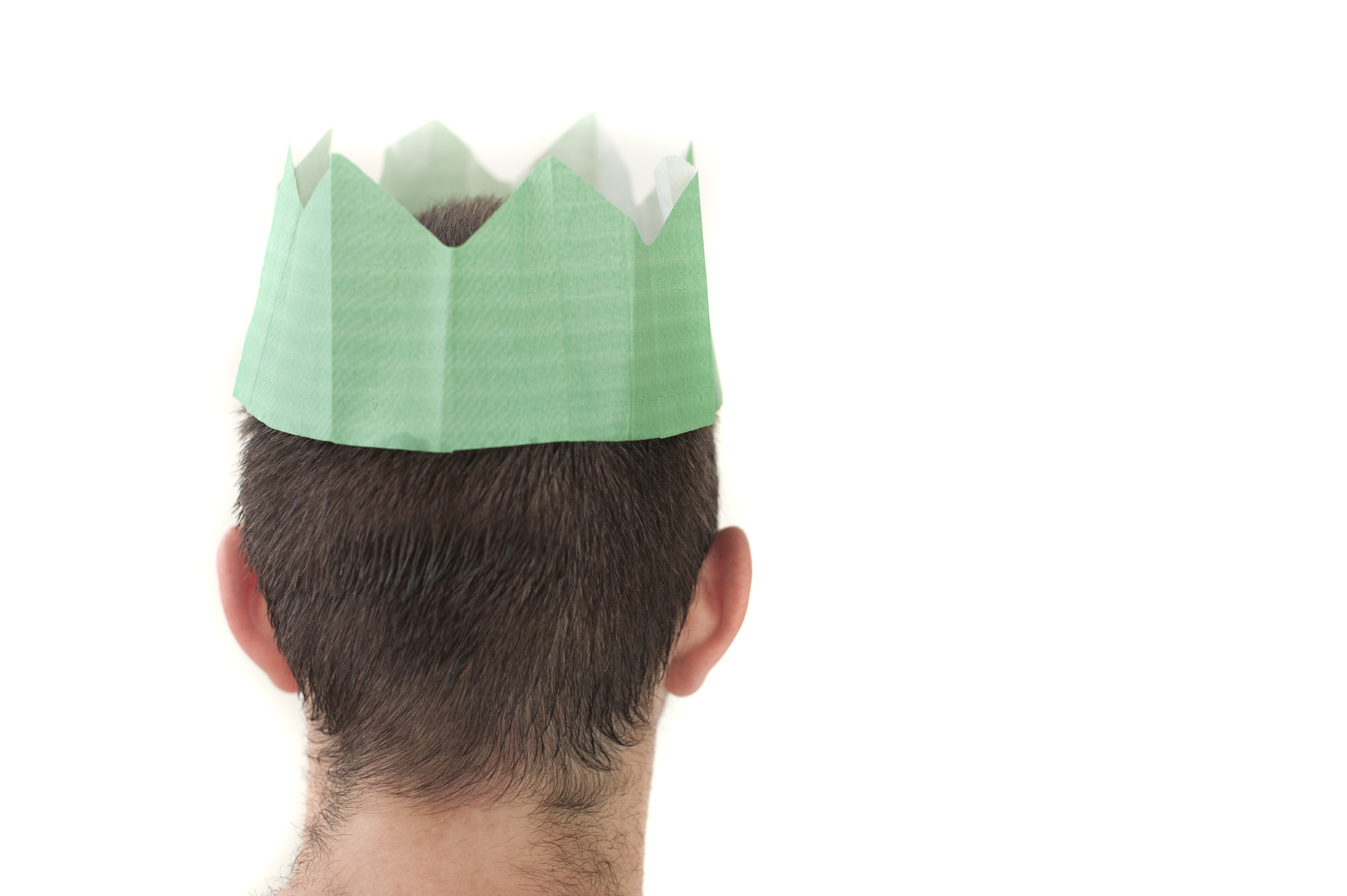 a man wearing a green coloured christmas party hat pictured against a white background