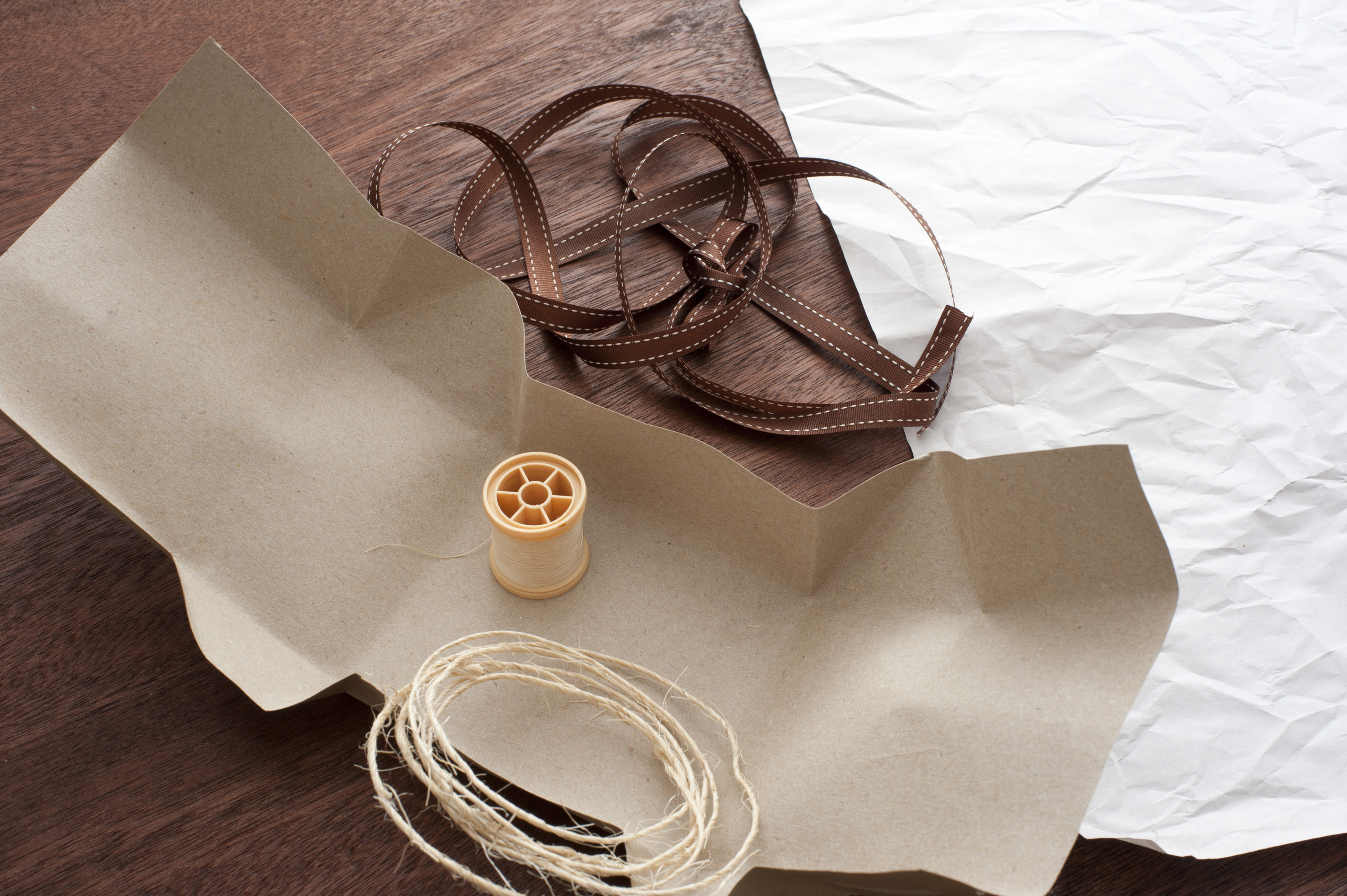 Close-up of wrapping paper and ribbon lying on wooden table. From above