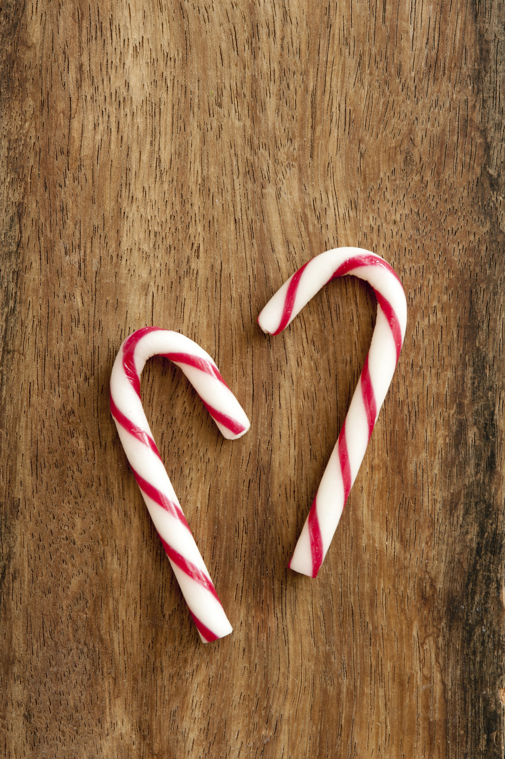Close-up of two sweet peppermint candycanes on wooden table. From above