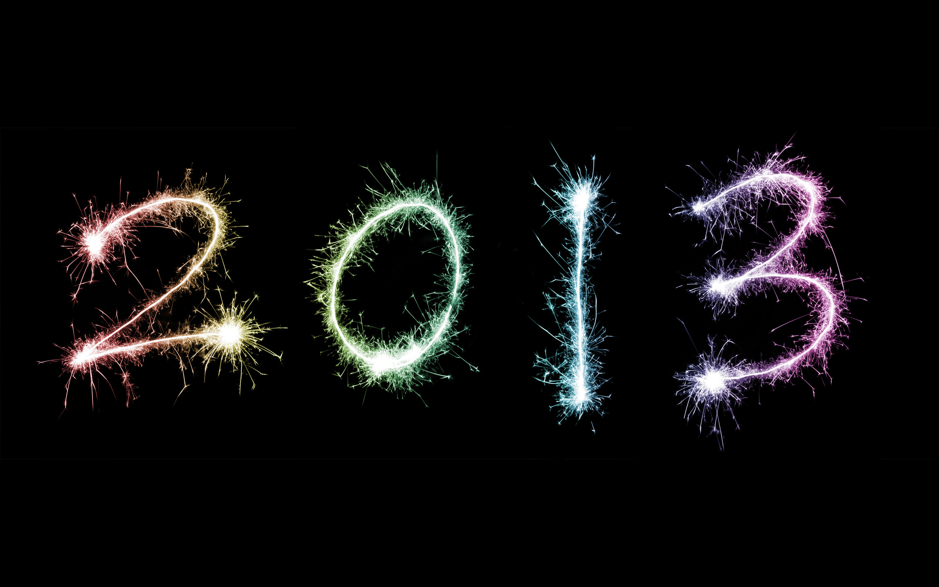 2013 written in colourful fiery sparklers against a black background for your New Year celebration or greeting card