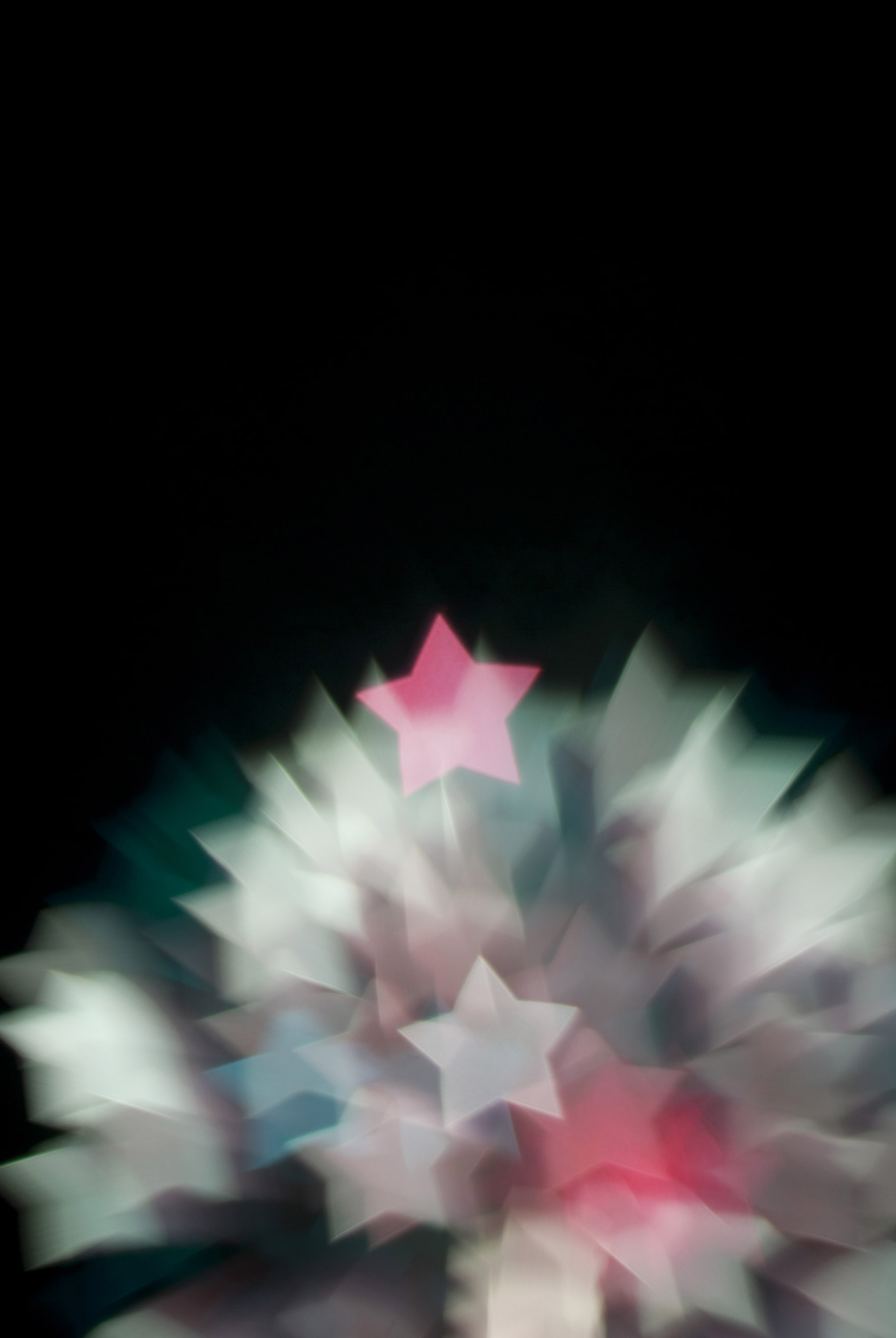 a defocused image of fireworks created with a star shaped gobo