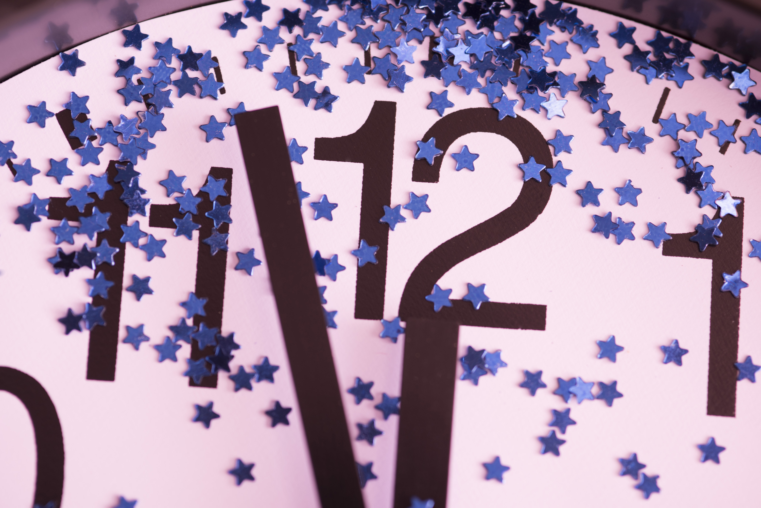 Countdown to midnight on New Years Eve with a close up view of a clock dial decorated with stars with the hands approaching the twelve