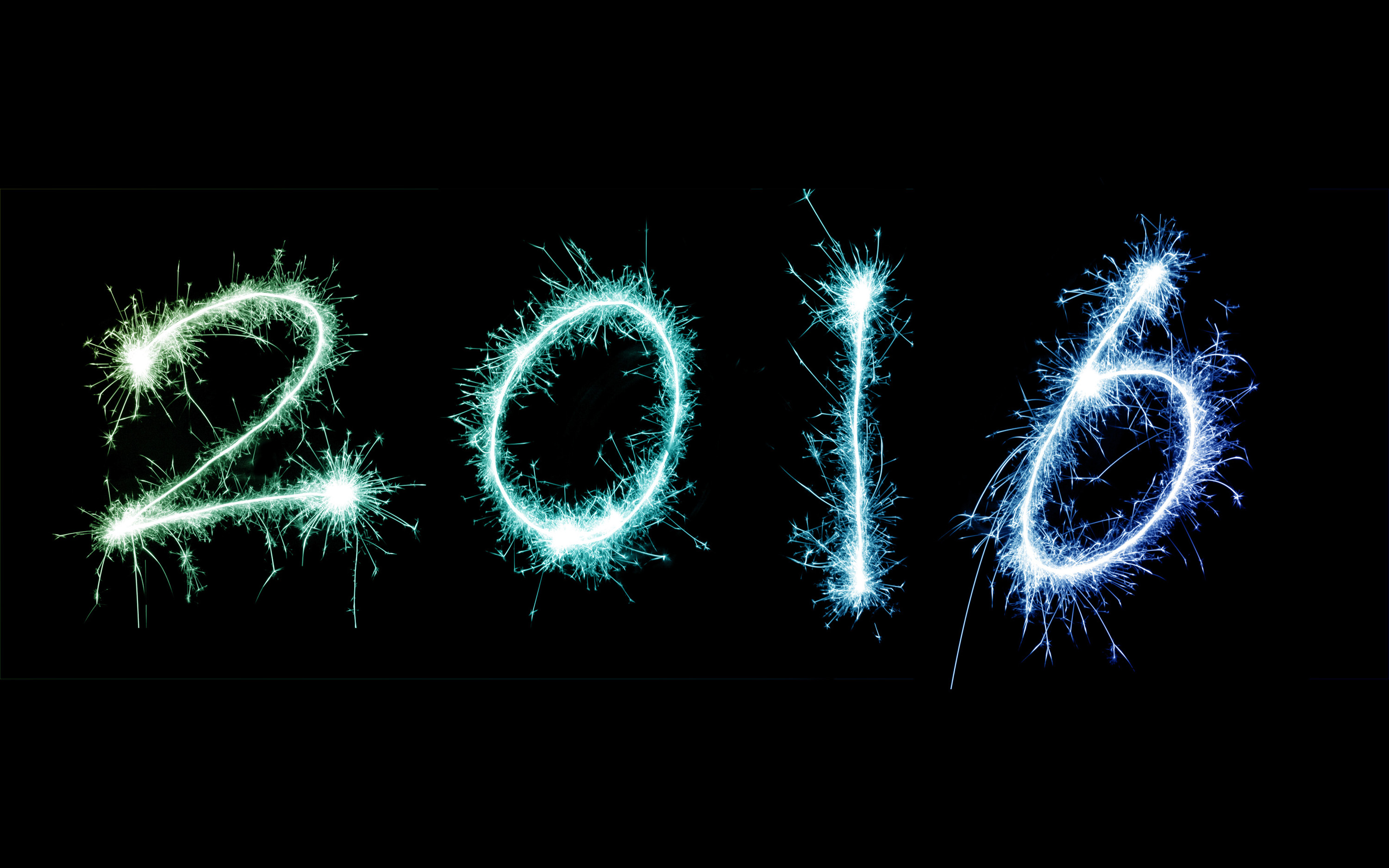 2016 New Year celebration display with the date outlined with fiery sparklers in green and blue on a black background