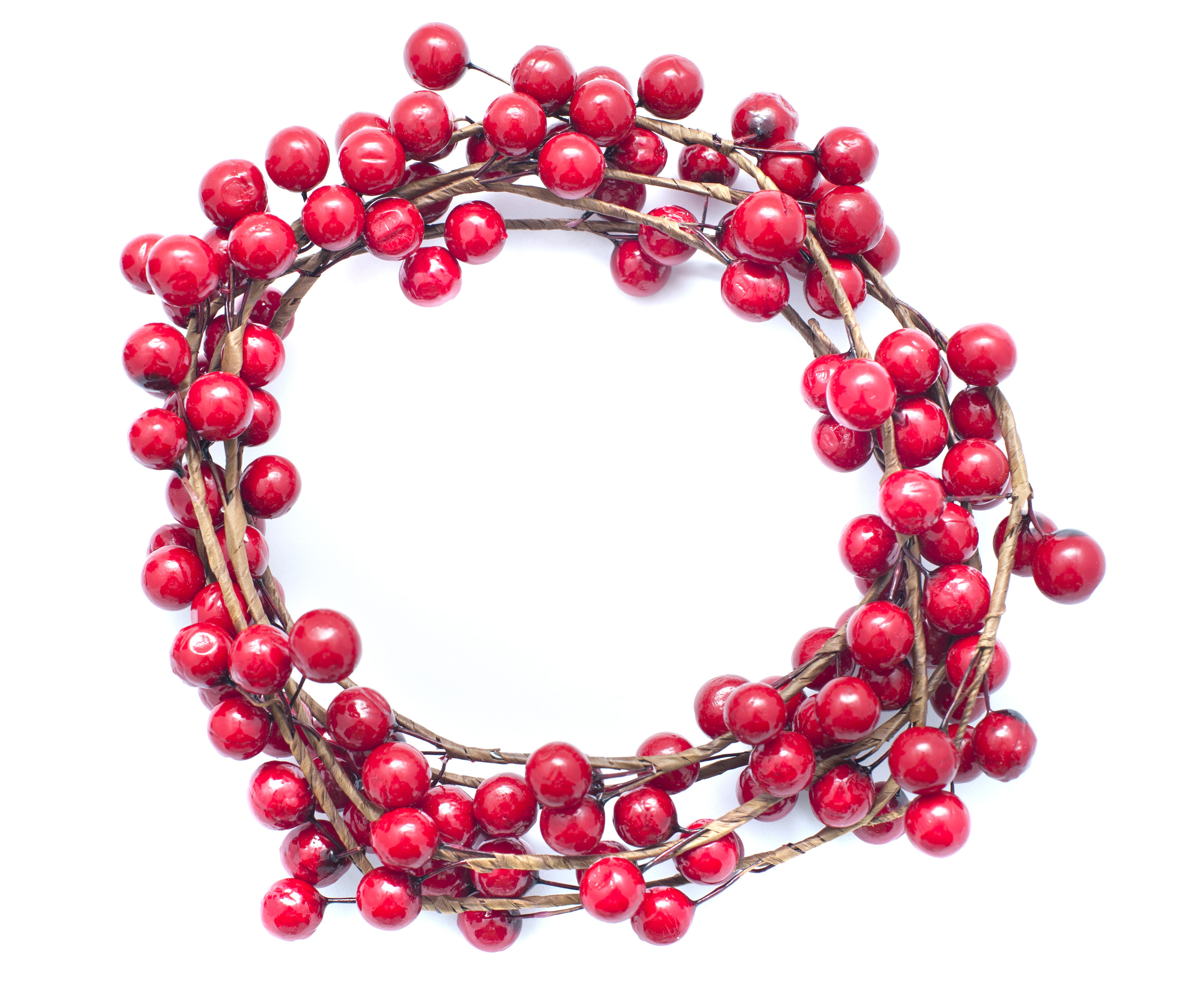 Circular wreath of colorful red Christmas berries isolated on white with central copy space for your holiday greeting
