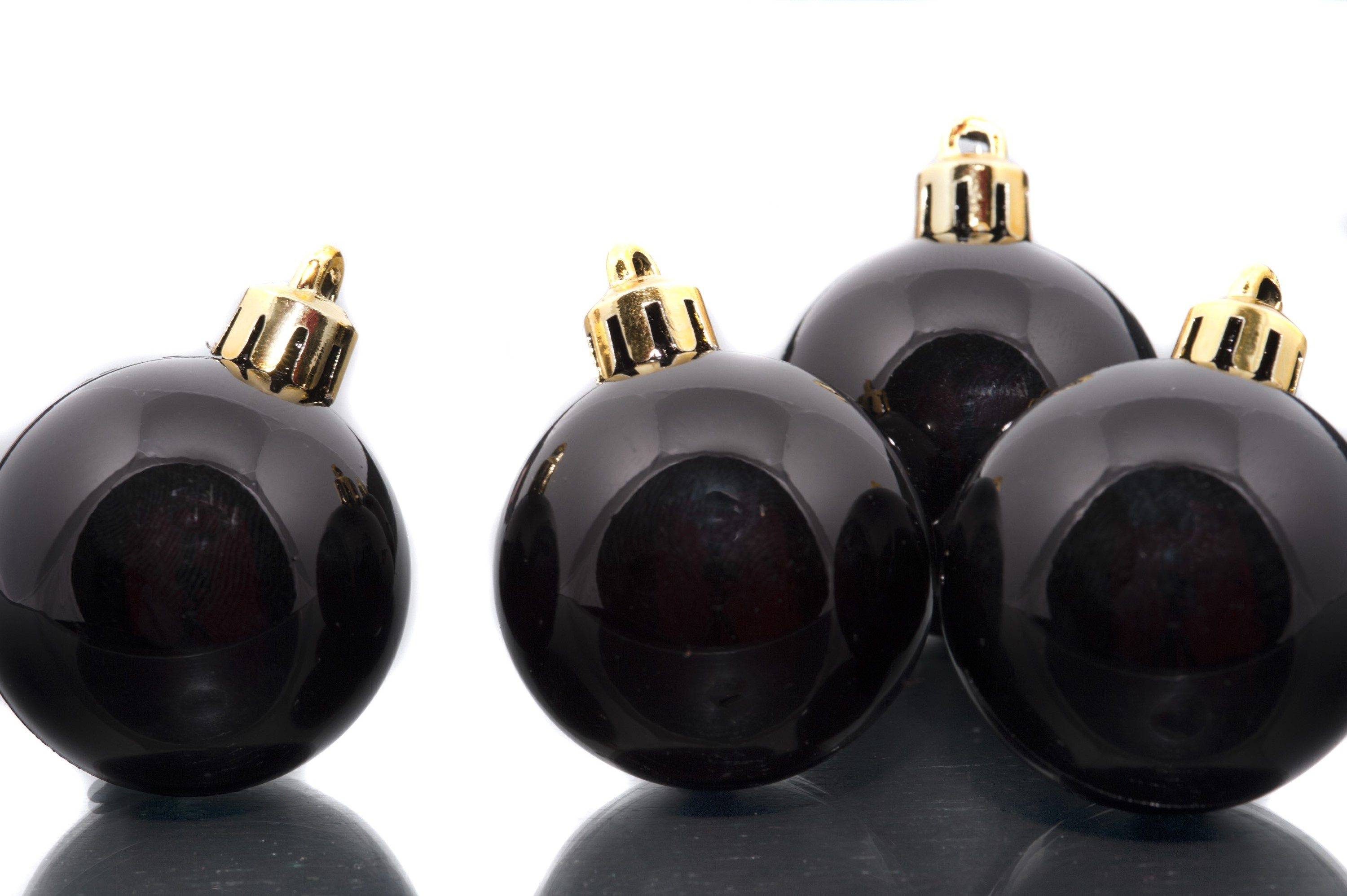 Black festive Christmas baubles lit from above with reflections on a white background