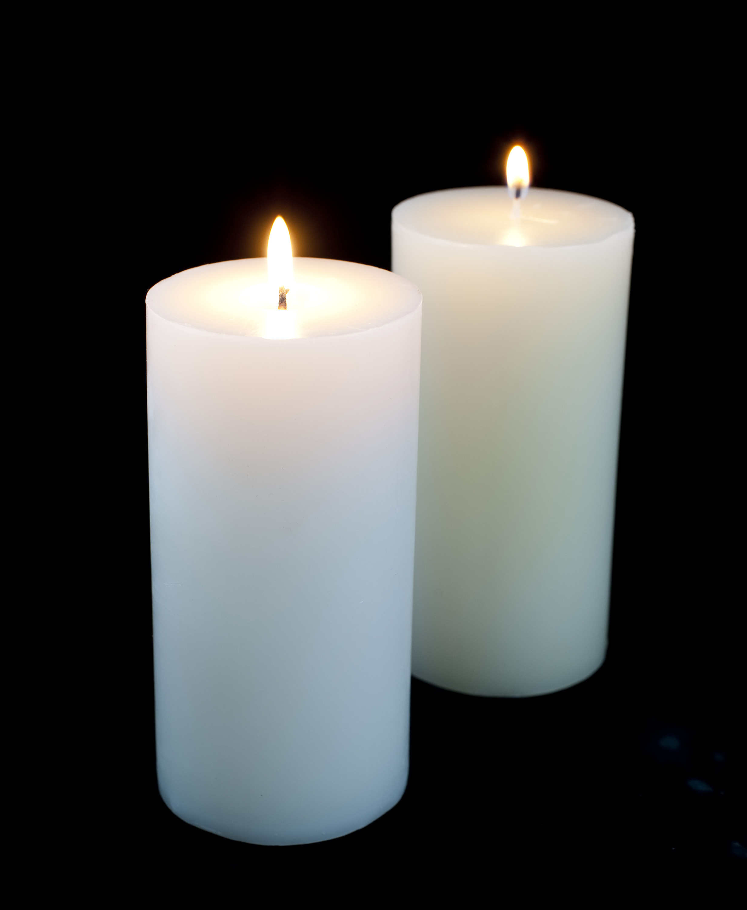 large white candles burning against a dark backdrop