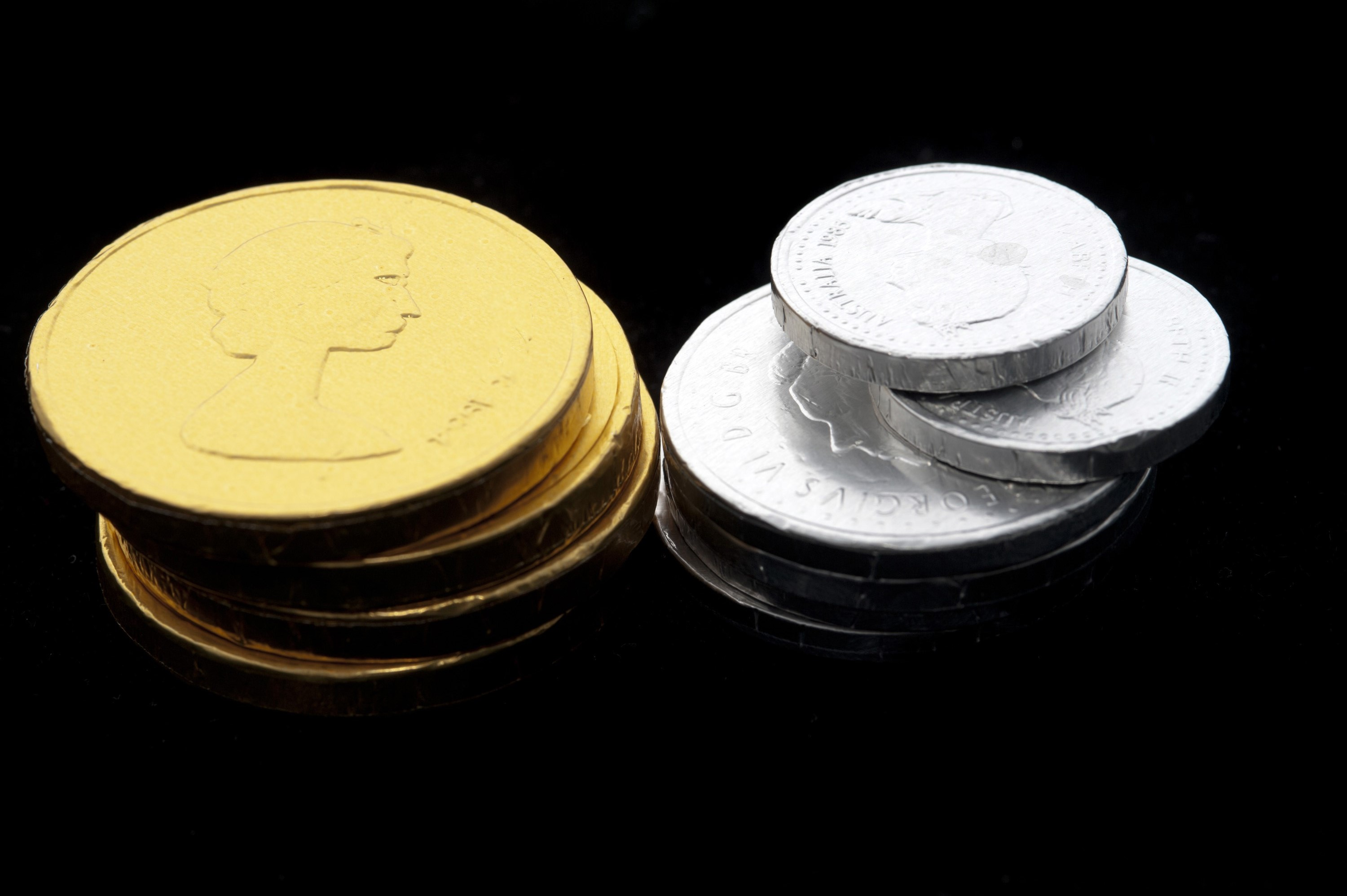 Stacks of chocolate candy coins wrapped in metallic silver and gold foil arranged on a black background