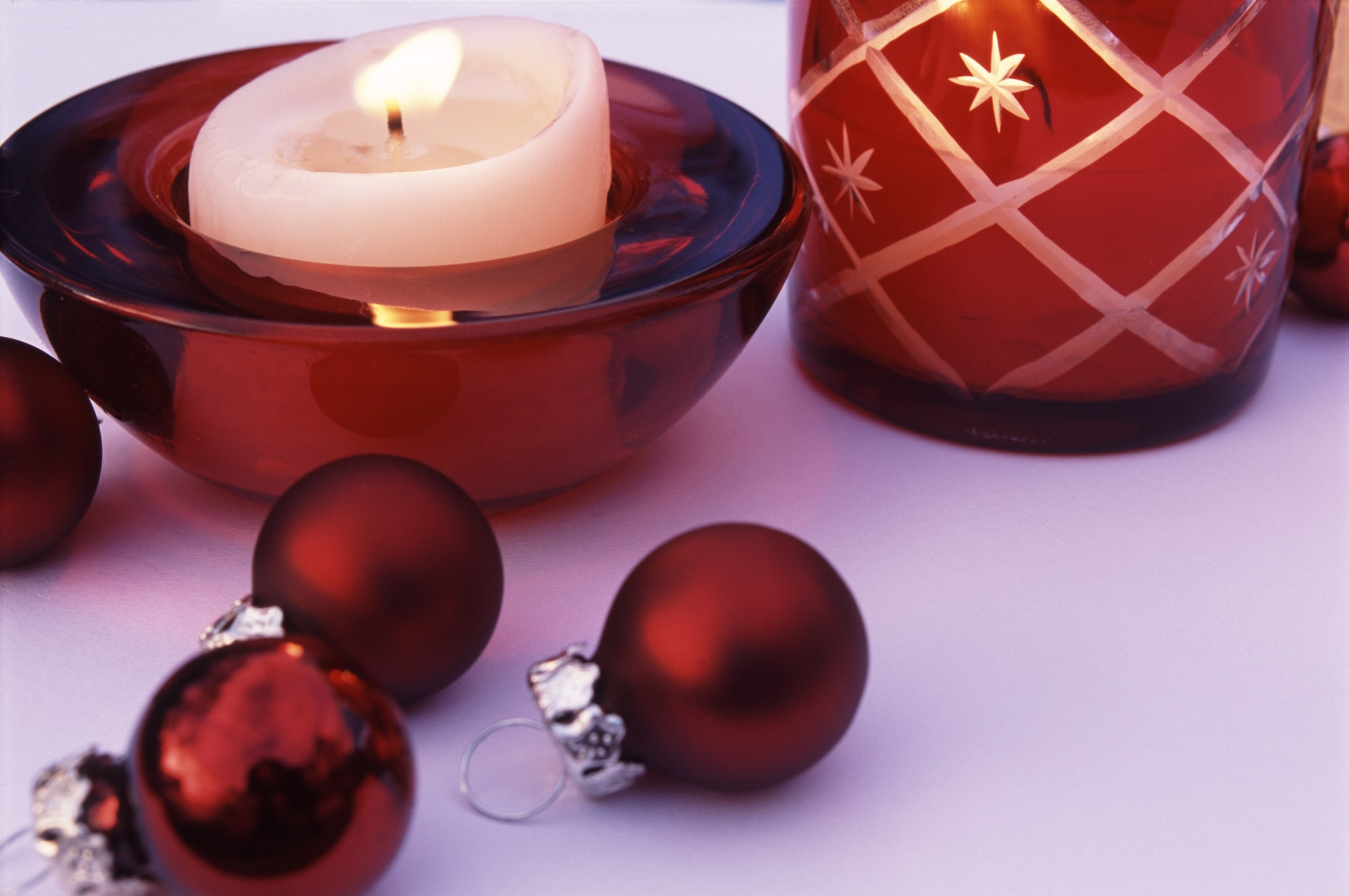 a red coloured festive still life composed of a candles glass holders, christmas balls and