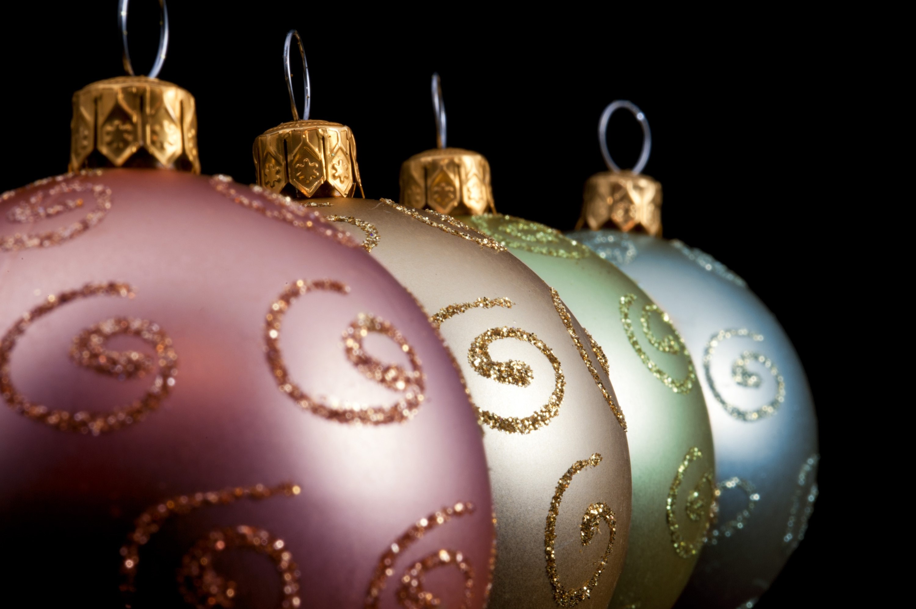 Receding diagonal row of decorative Christmas baubles with selective focus to the second ball on a dark background