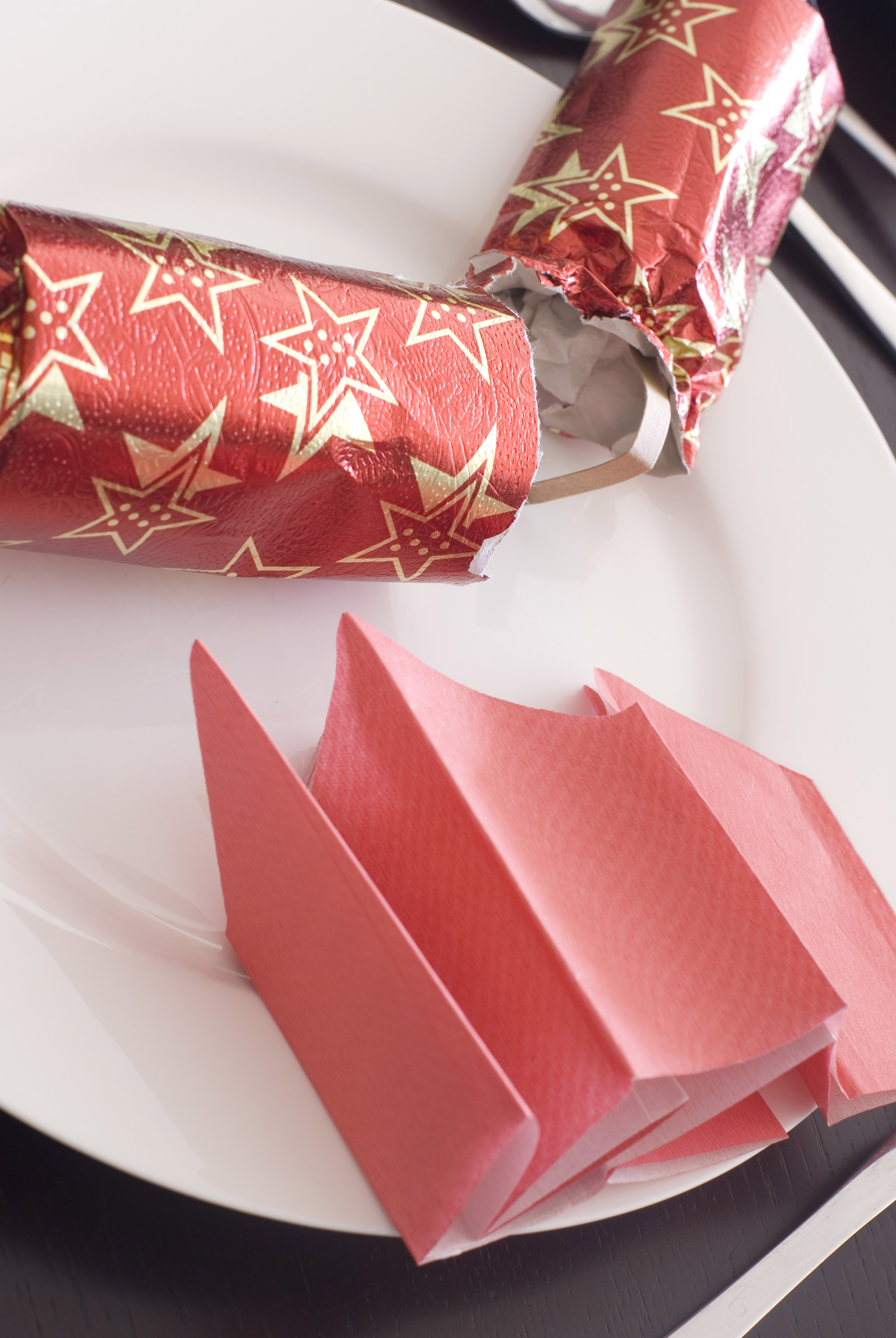 a 'snapped' christmas cracker and red paper party hat