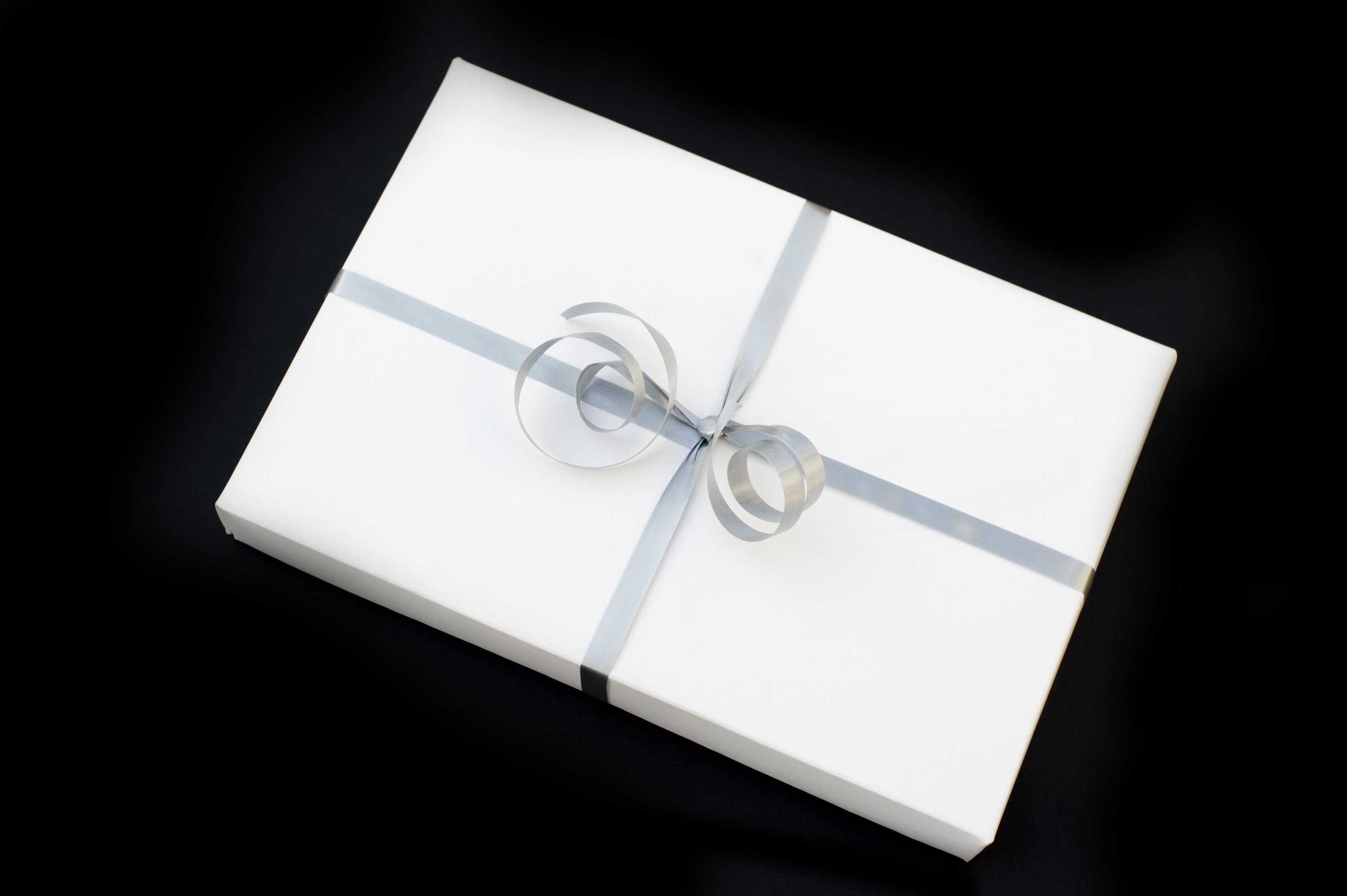 a white wrapped christmas gift with a silver bow against a black backdrop