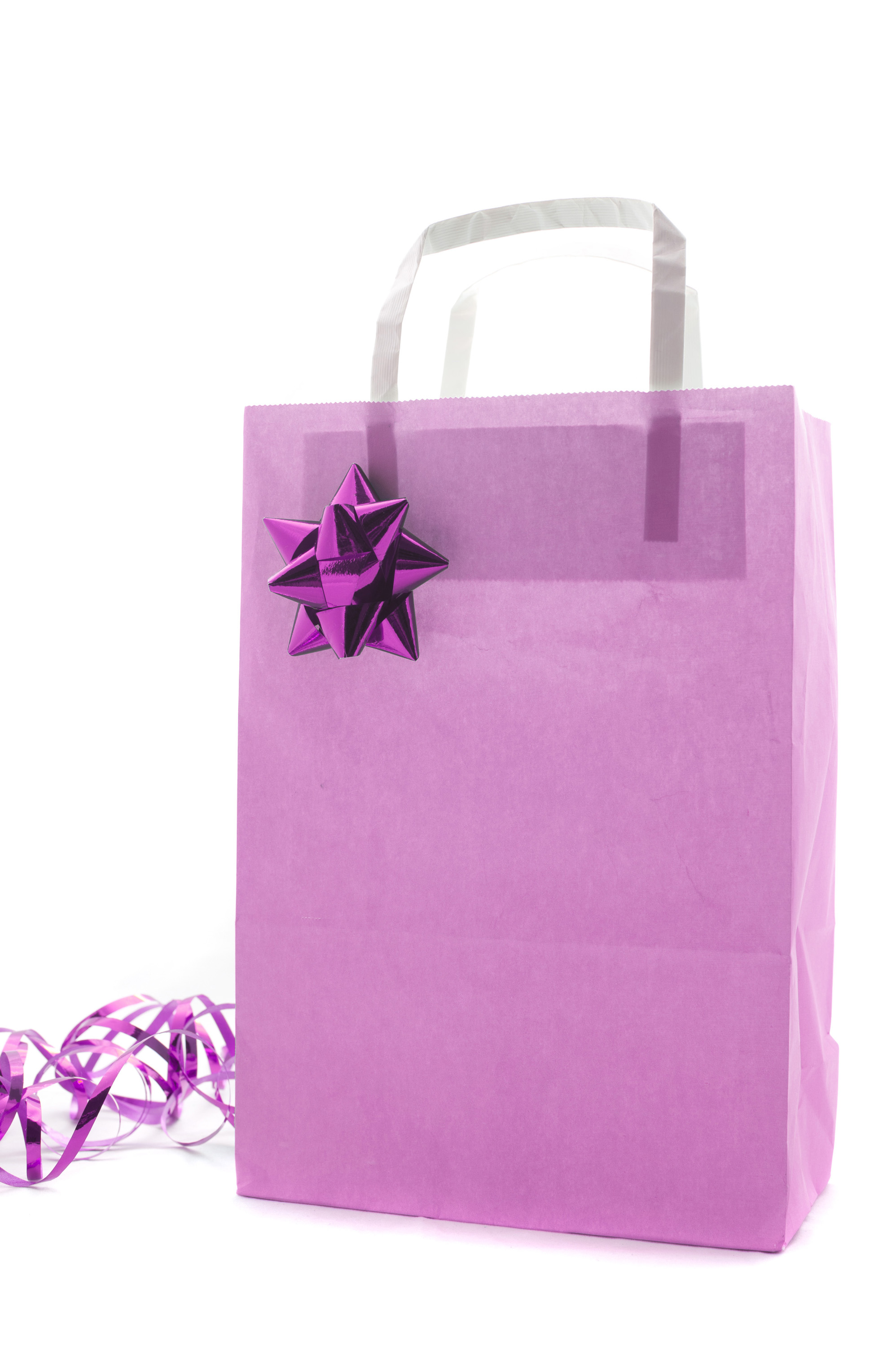 Pink Christmas shopping or gift bag decorated with a metallic bow and twirled ribbon isolated on a white background