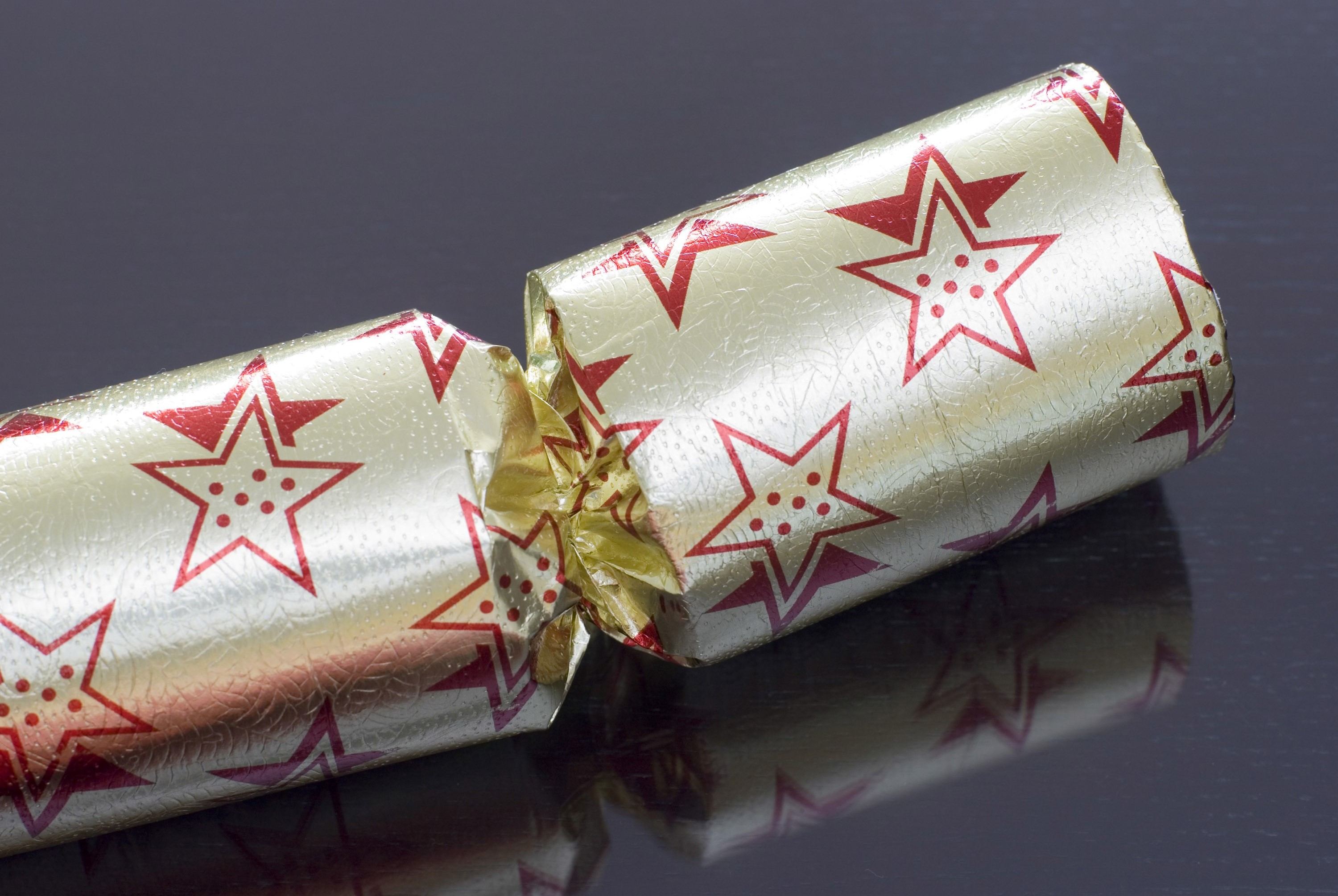 closeup on a gold coloured christmas cracker on a dark background