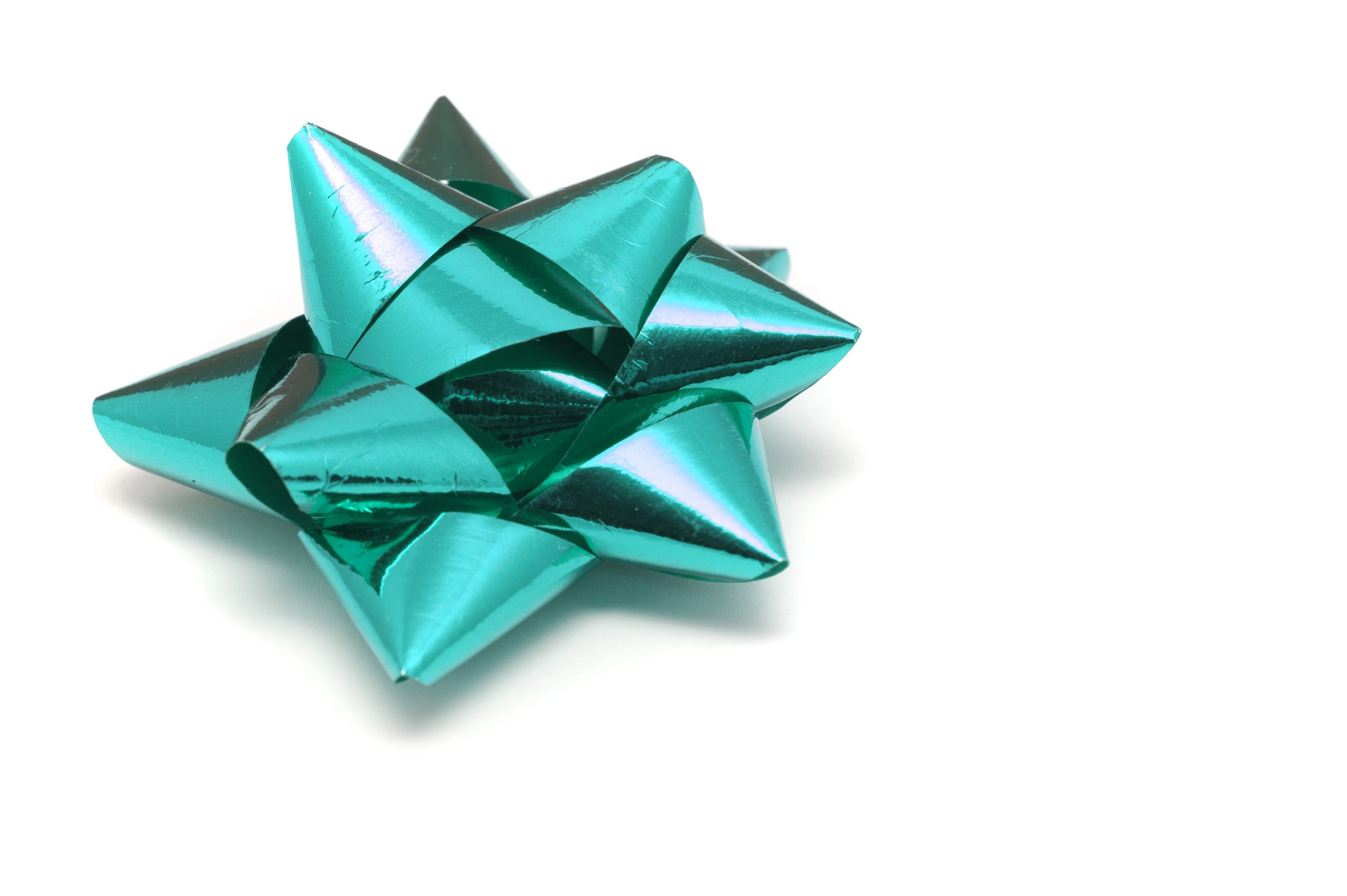 Ornate cyan bow made from metallic foil ribbon for gift wrapping and decorating seasonal and Christmas gifts for loved ones on white with copyspace