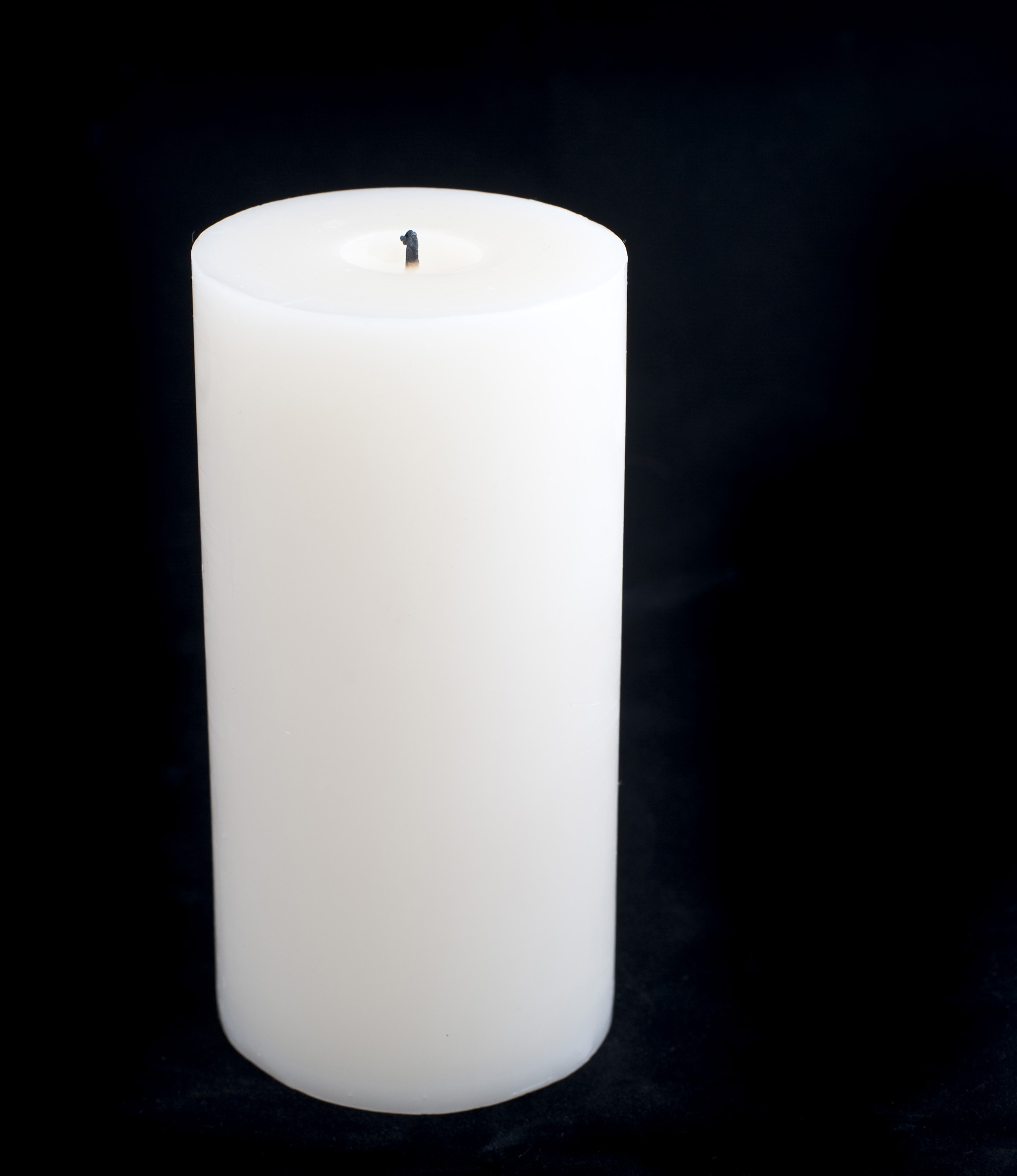 a large pillar candle unlit on a black background