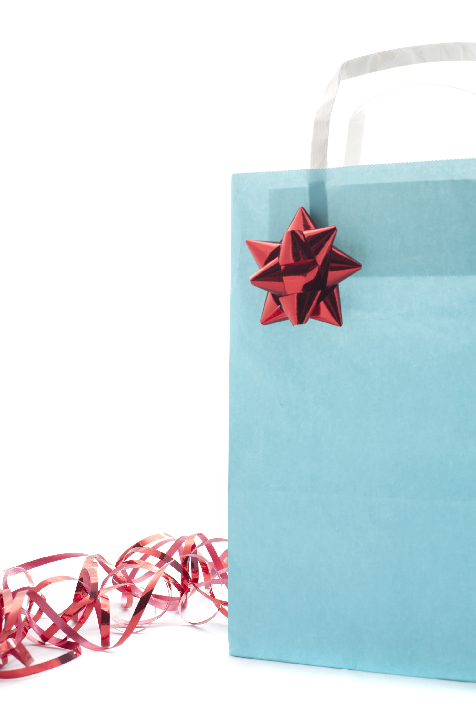 Decorated blue gift bag with an ornamental red bow and ribbon to celebrate a special occasion with a loved one isolated on white, close up view