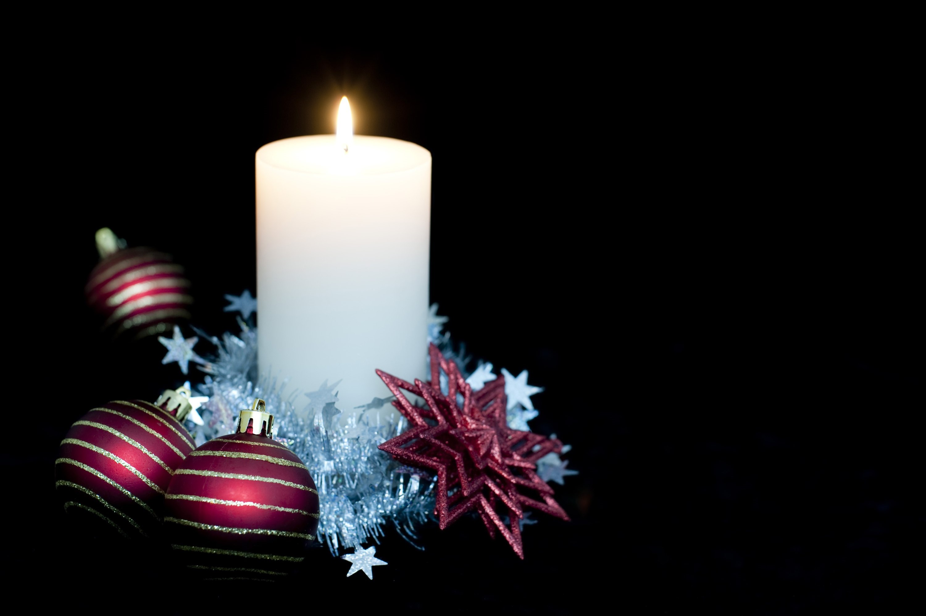 a large candle surrounded by seasonal decorations with lots of copyspace to the right