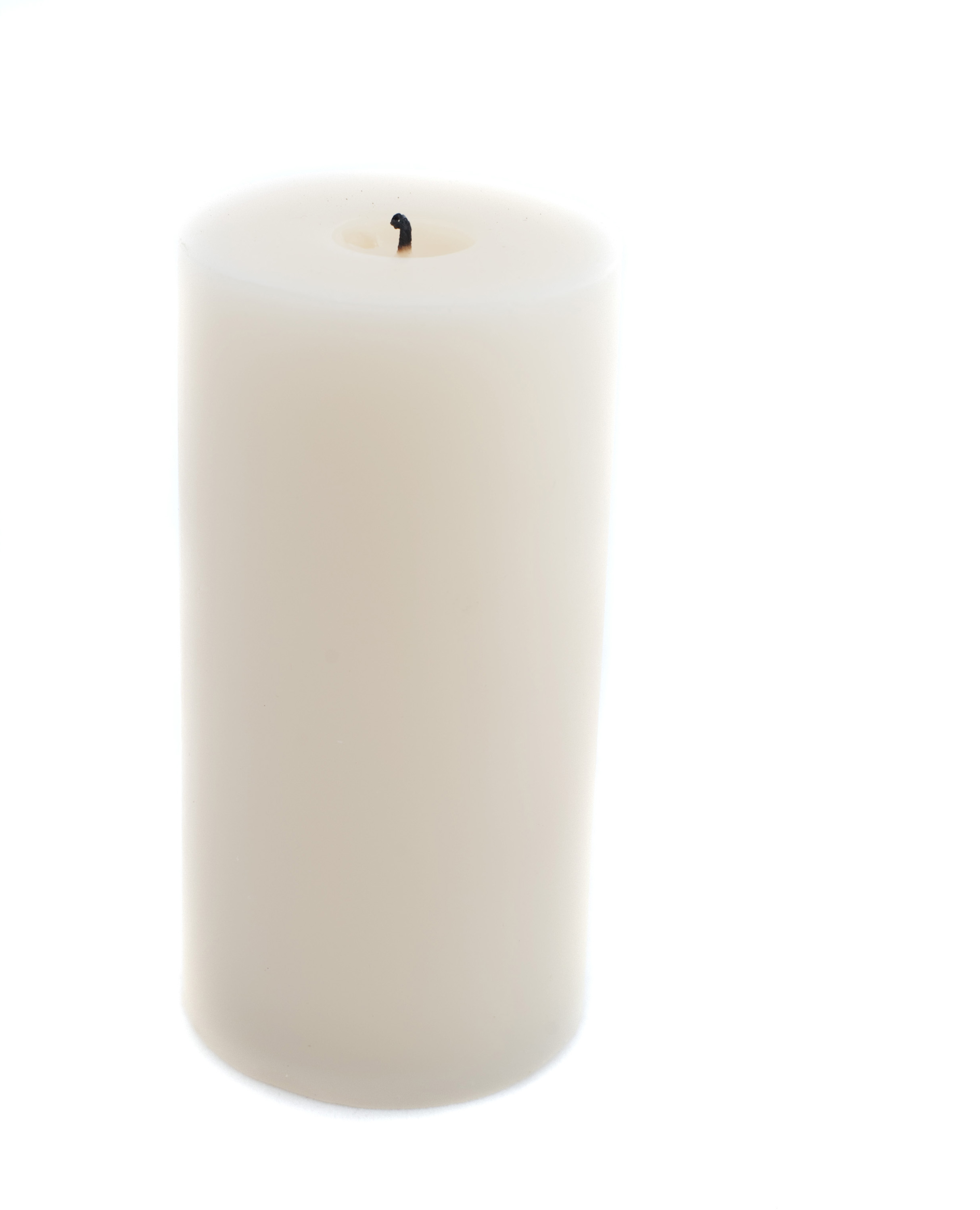 a large pillar candle unlit on a white backdrop