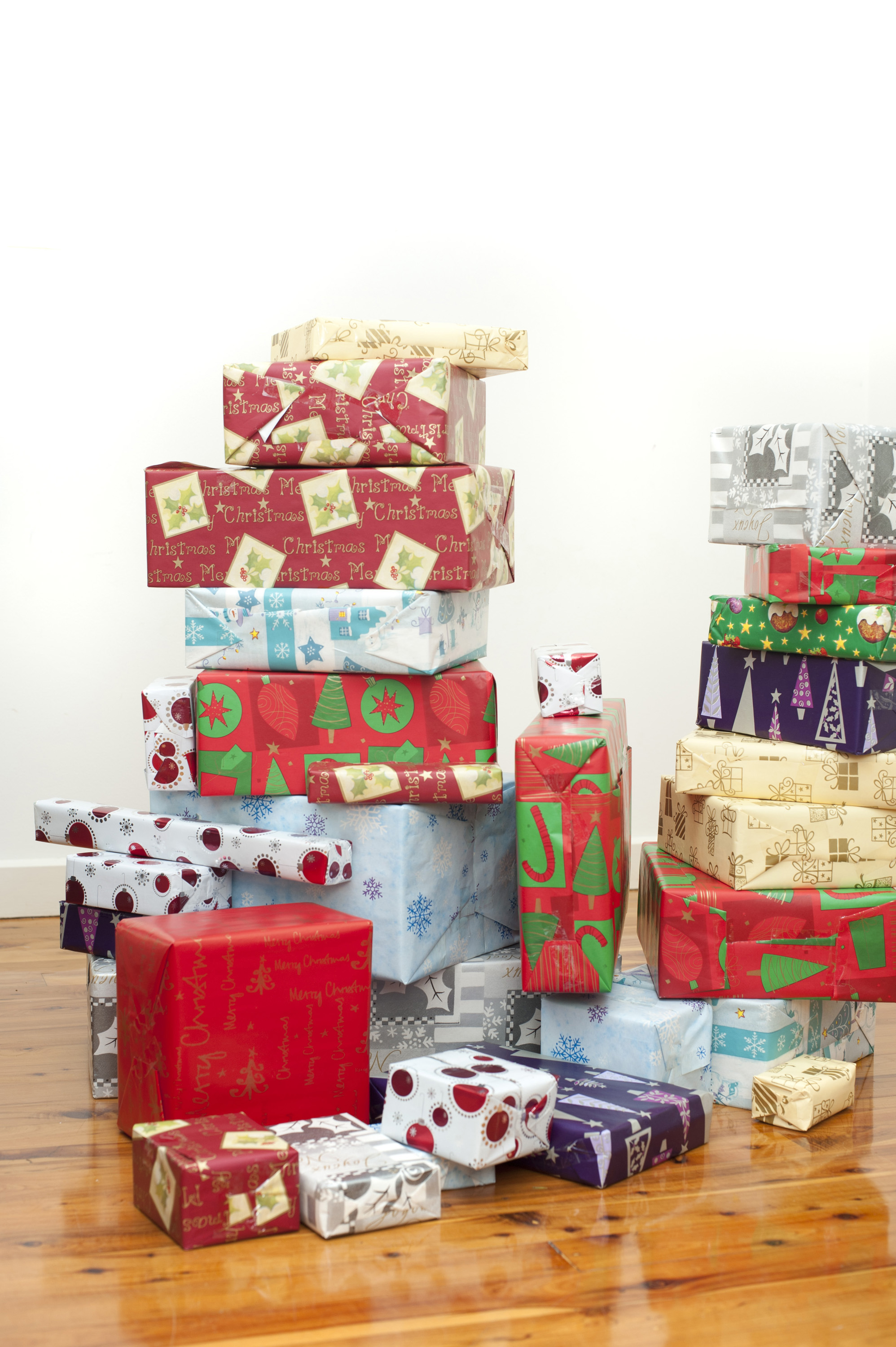 Stacks of multicoloured Christmas gifts wrapped in a variety of colourful paper with seasonal patterns standing on a hardwood floor in the house