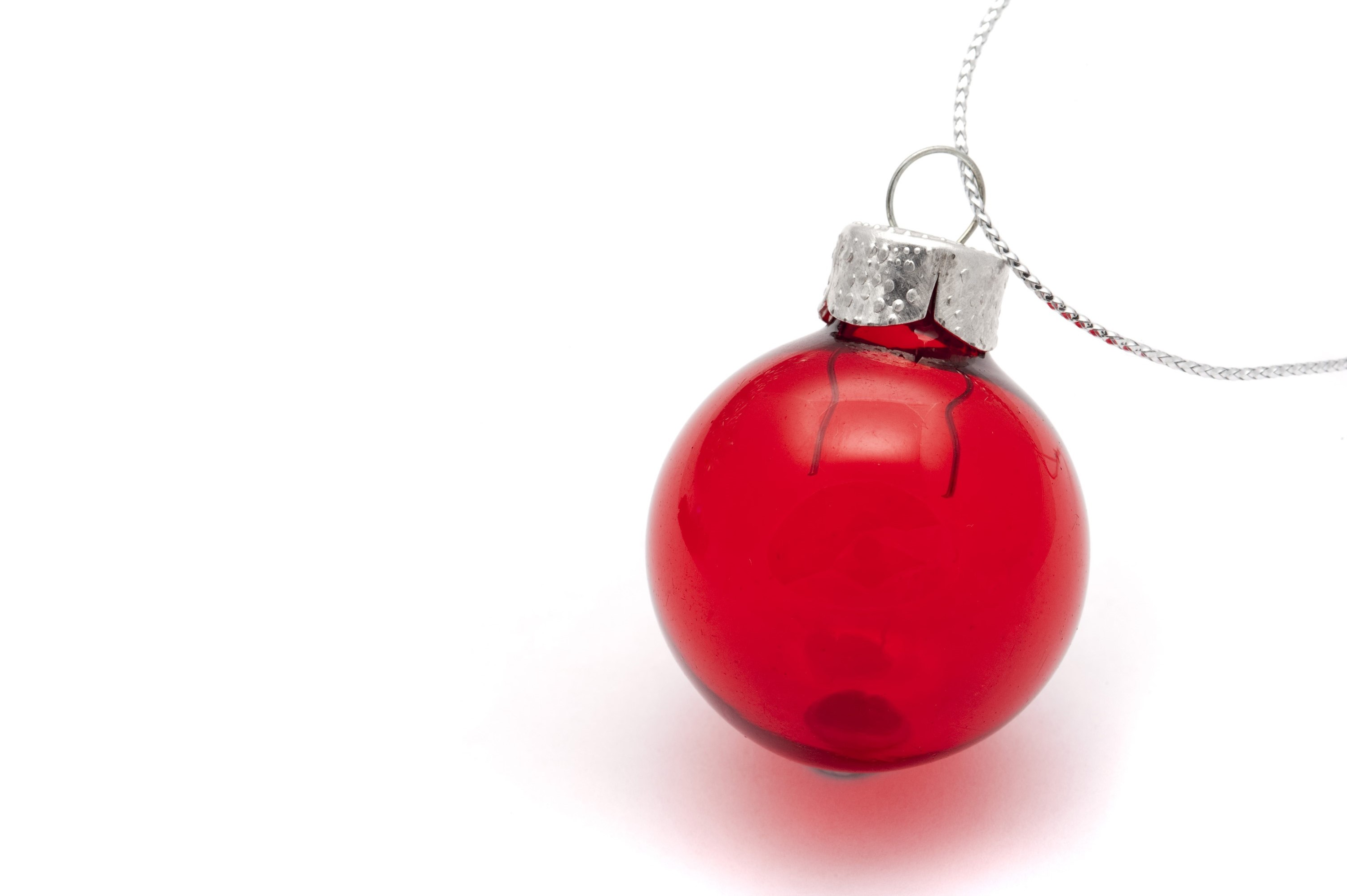 a red colored glass christmas decoration on a white background