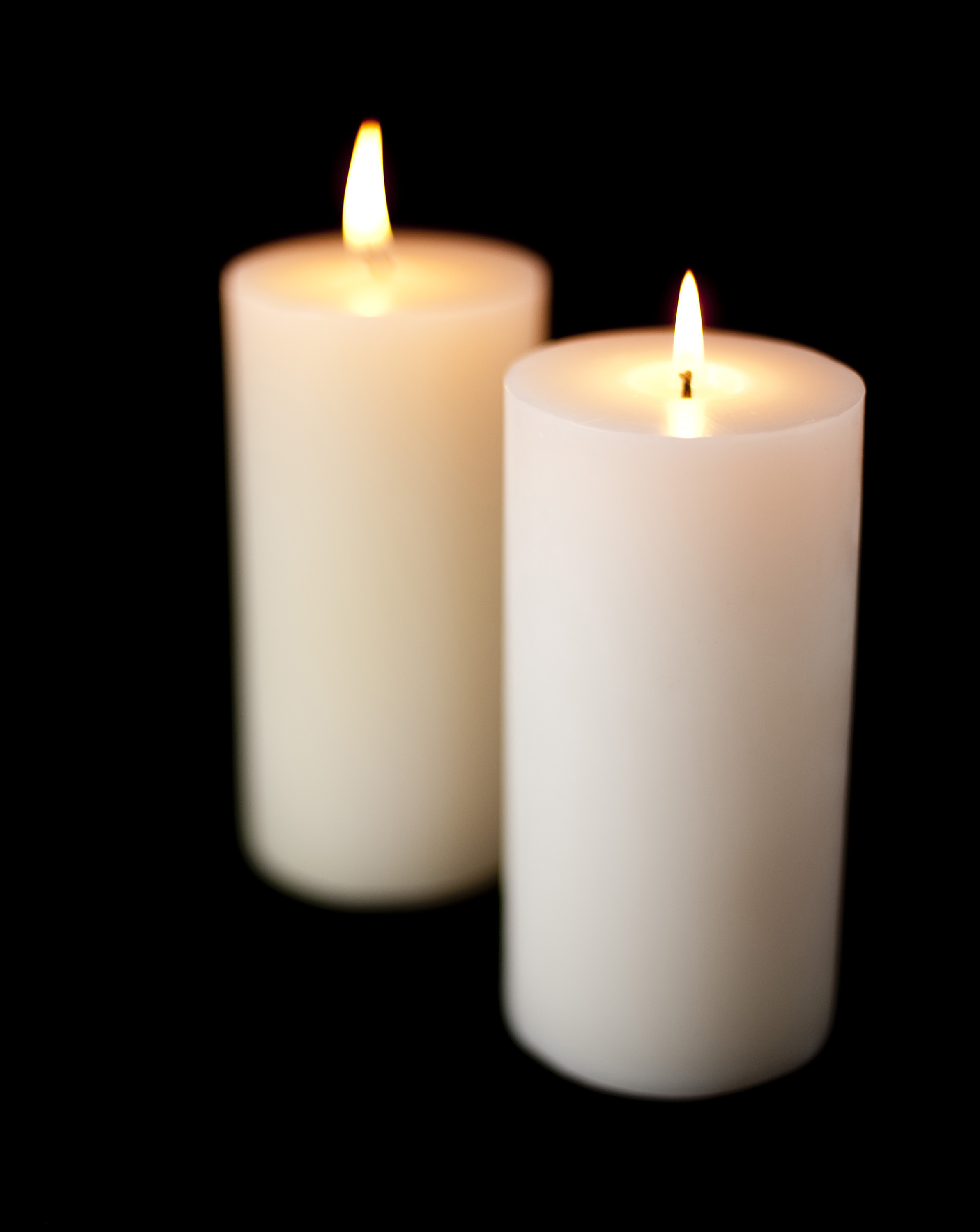 large white candles burning against a dark backdrop, pictured with a narrow depth of field to create a cosy homely effect