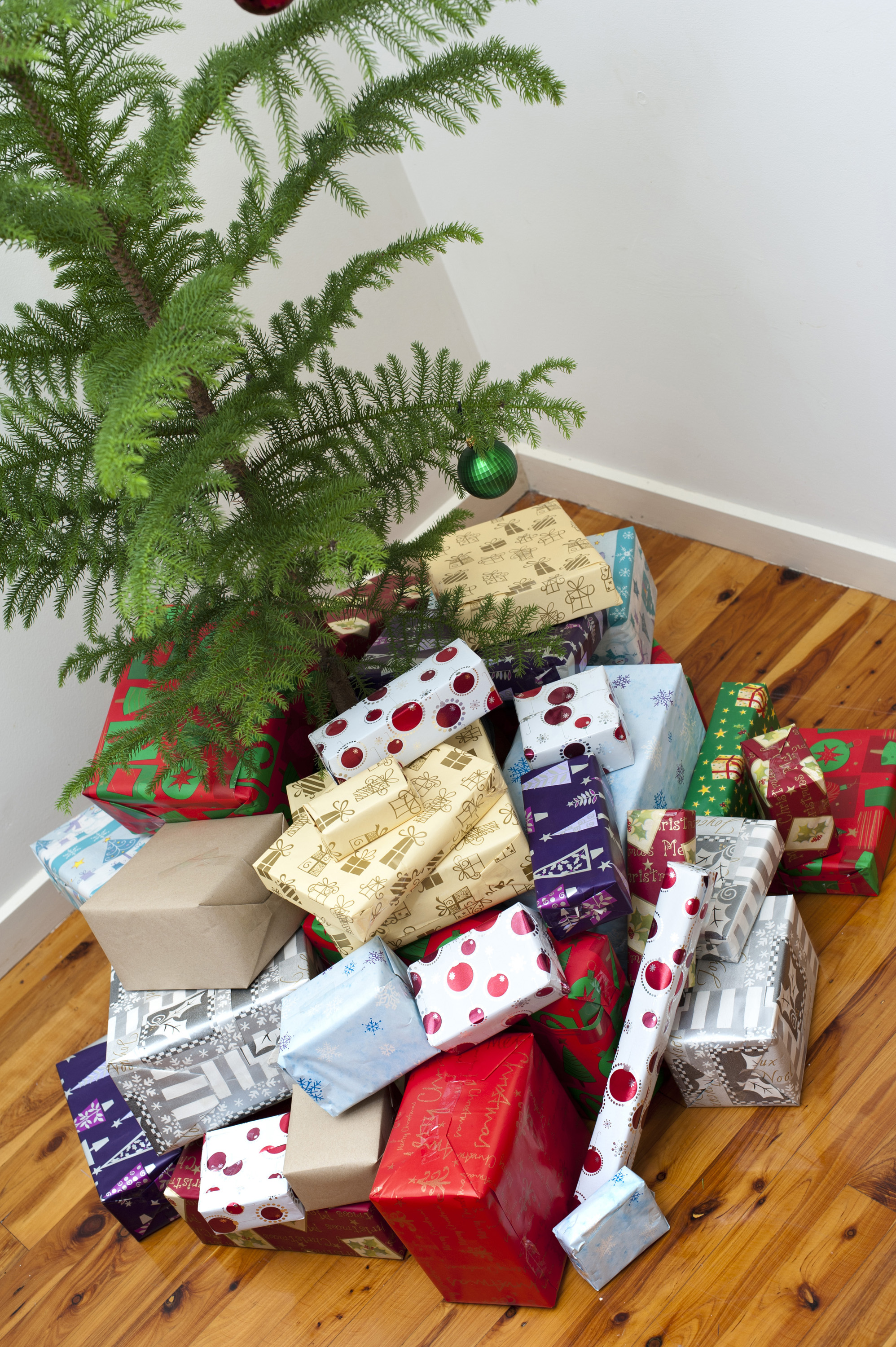 Large collection of colourful gift-wrapped Christmas gifts under a small Xmas tree in preparation for a family celebration of the festive season