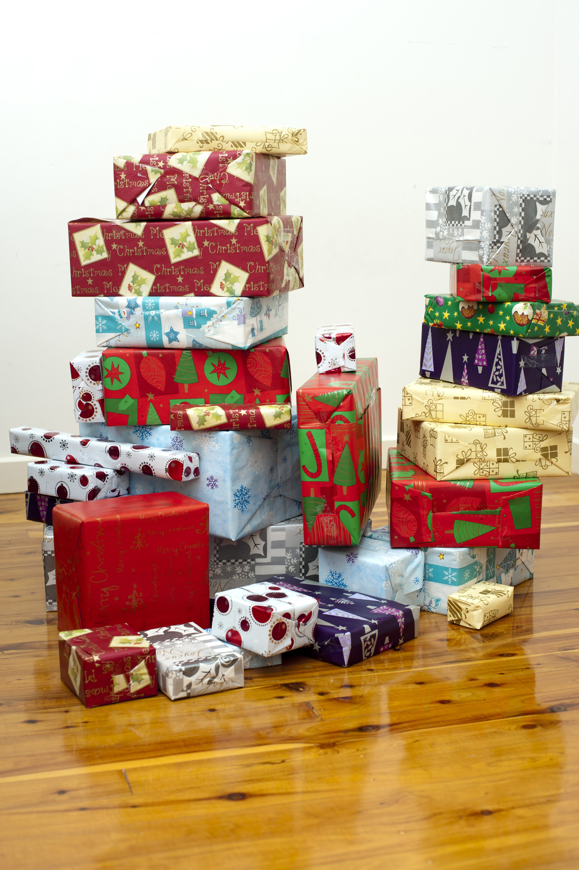 Stacks of colourful Christmas Gifts for the family piled on a polished hardwood floor waiting for Christmas Eve and the coming of Santa Claus
