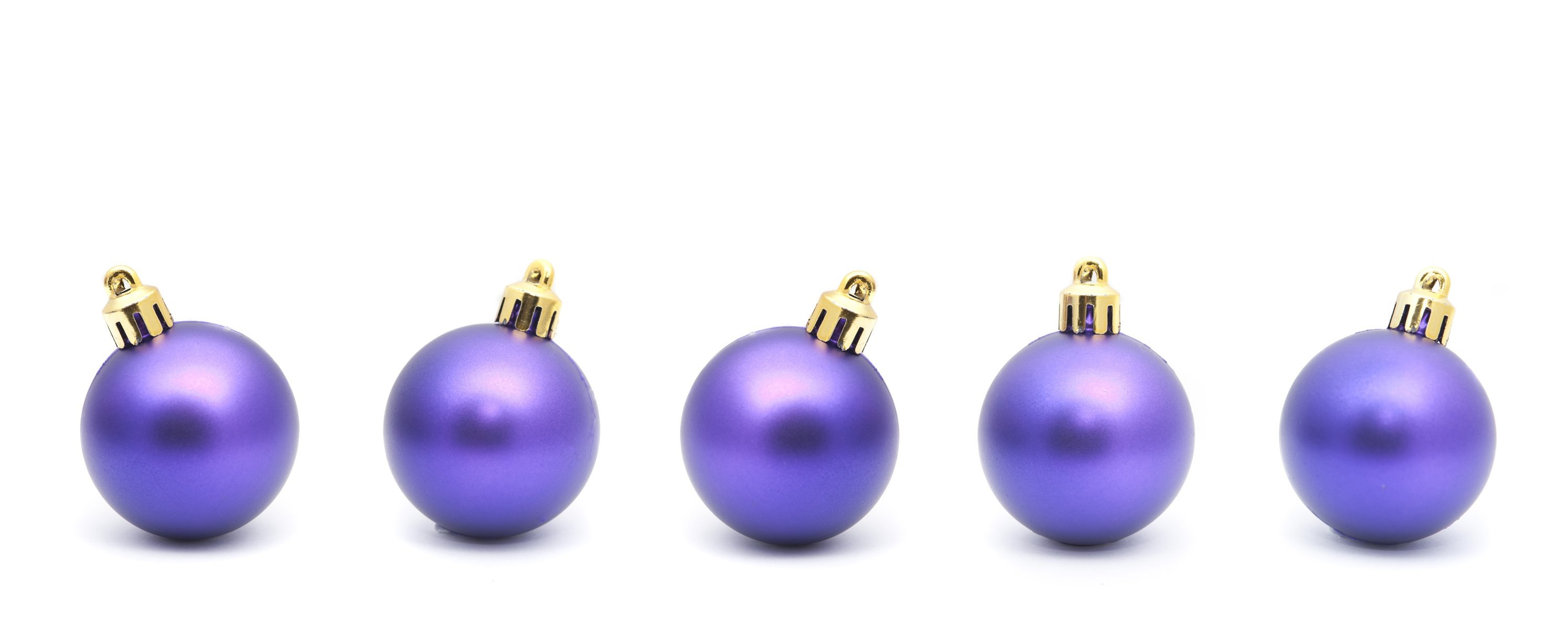 Purple Christmas bauble border with a row of five balls with natural shadow on a white background