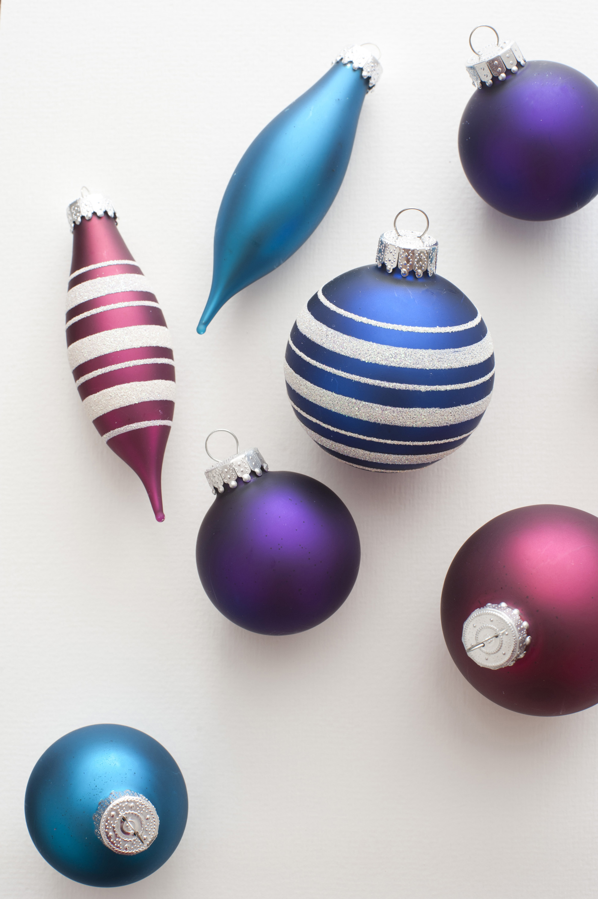 Close-up of seven colorful Christmas balls on white background. From above