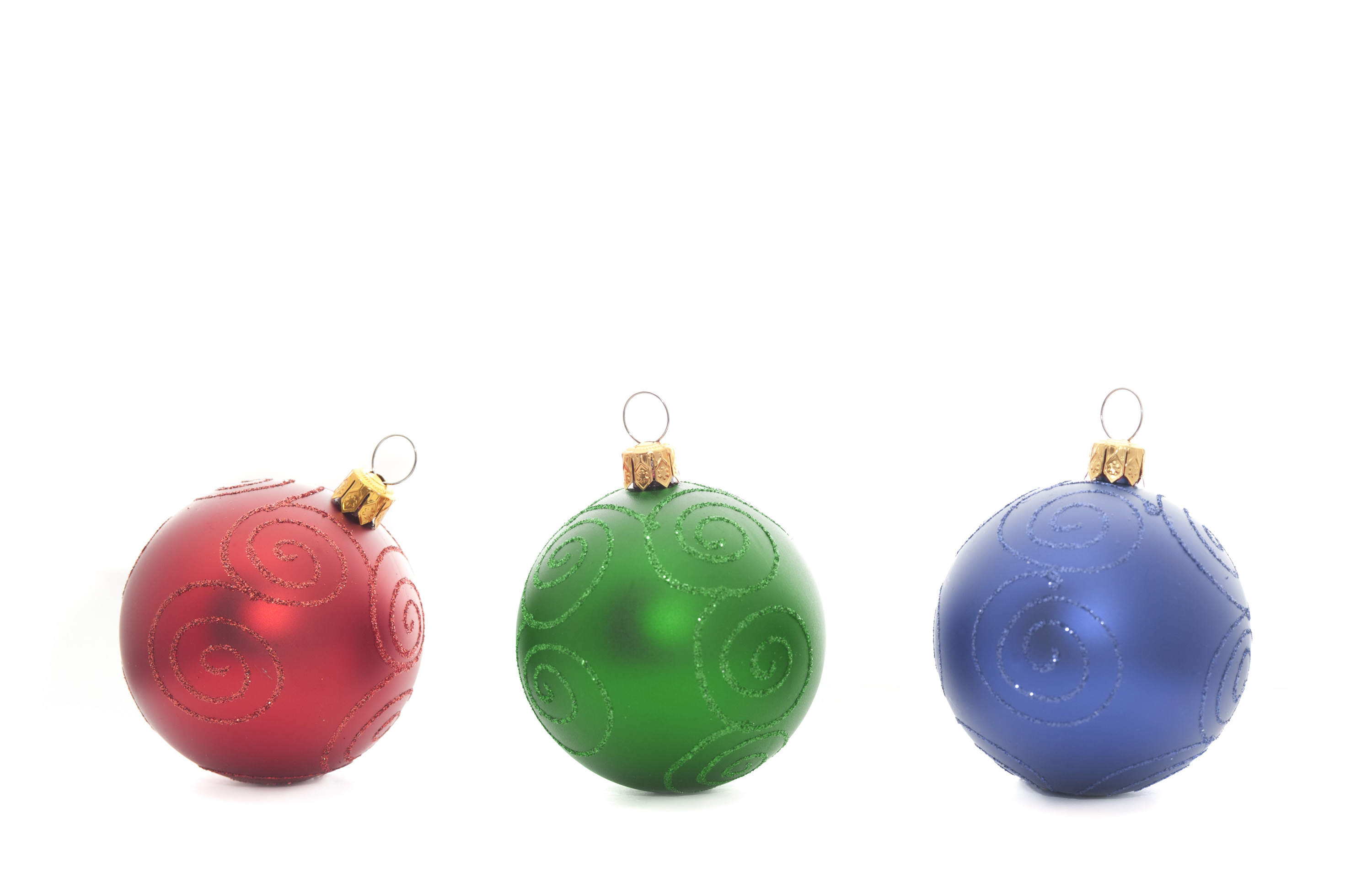 Red, green and blue baubles in a row on a white background with copyspace for your Christmas greeting or message