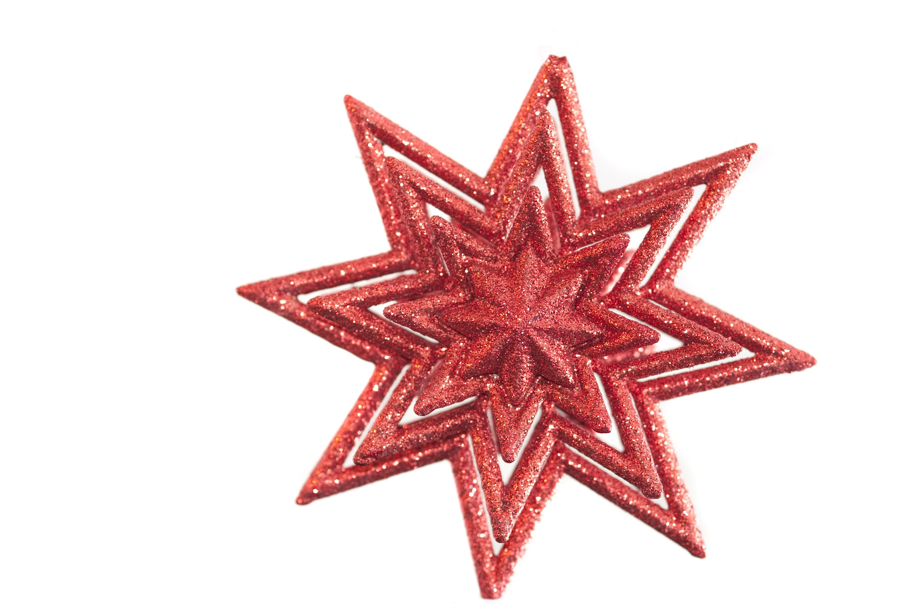 a red star shaped christmas decoration isolated on a white backdrop