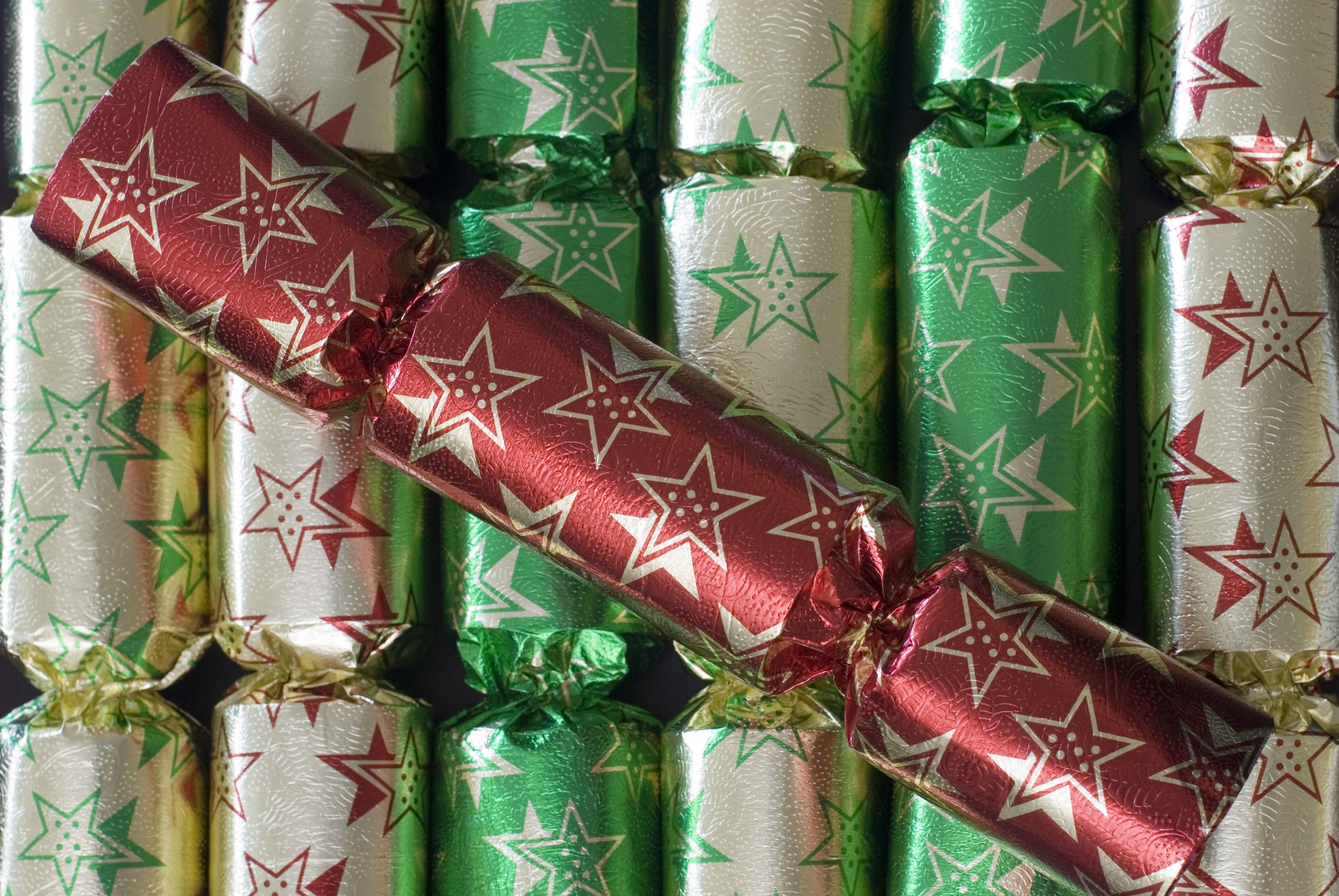 a background of christmas crackers with a single red christmas cracker on top