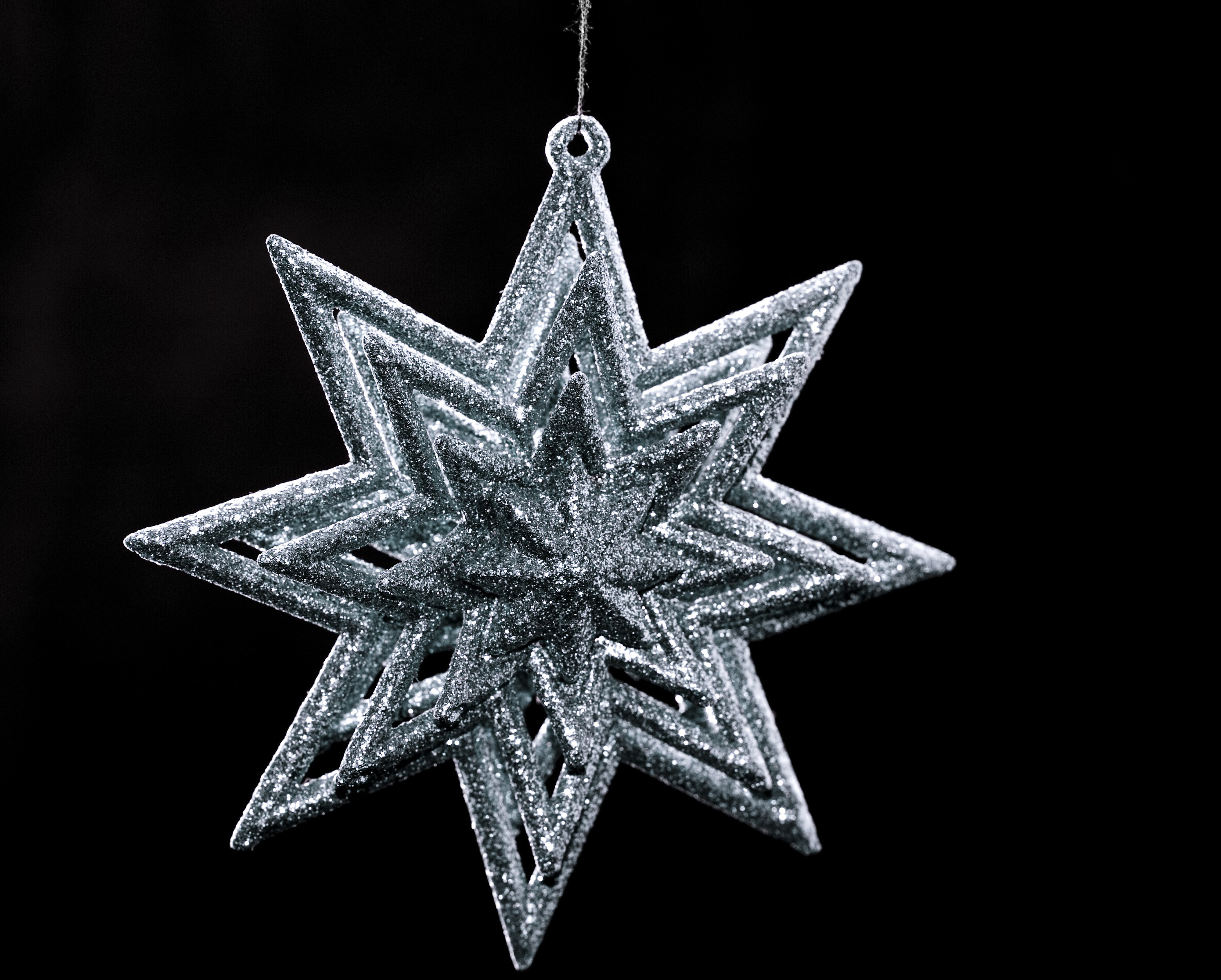 a silver glitter covered christmas tree hanging ornament