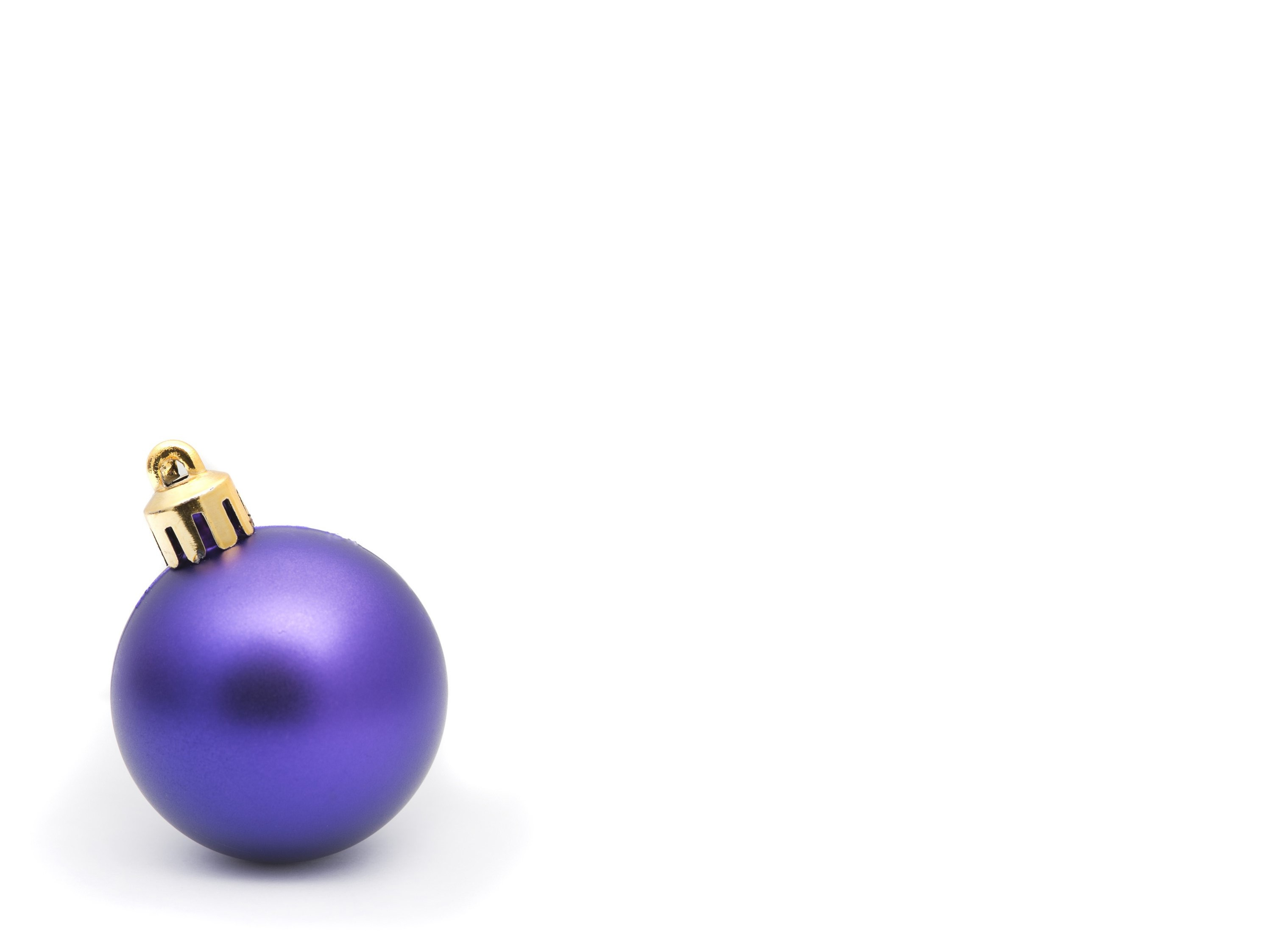 Single purple Christmas bauble to the bottom left of the frame with huge white copyspace for your Christmas message