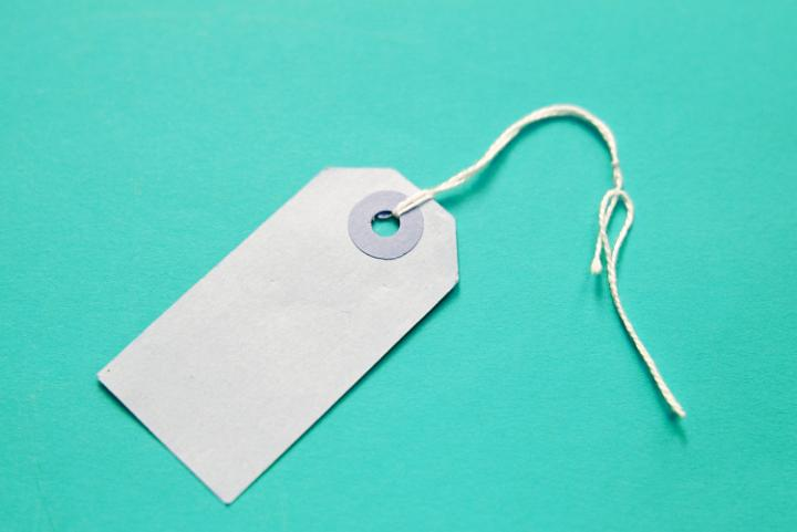 a plain white undecorated gift label on a turquoise backdrop