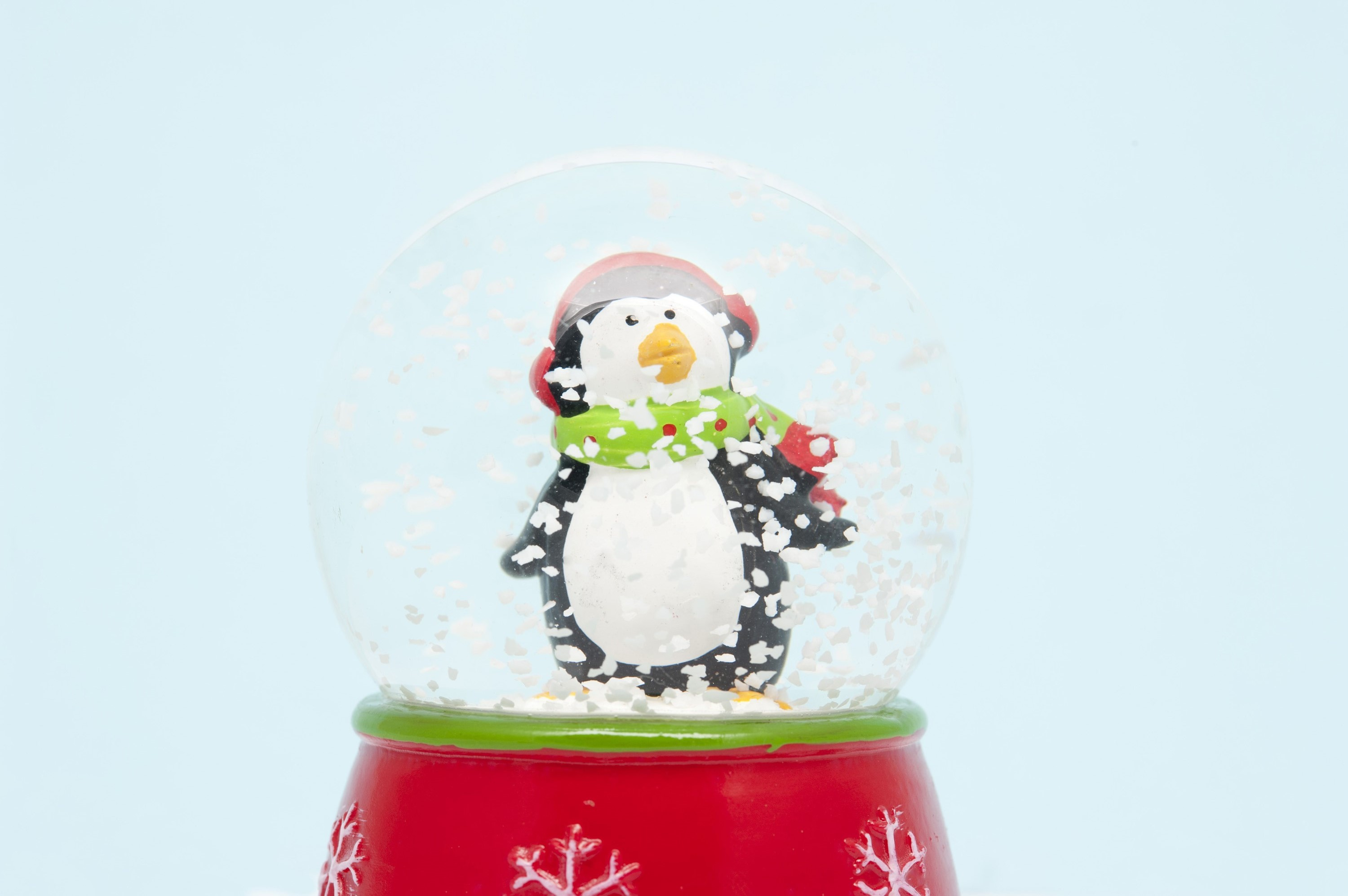 Cute little penguin in a winter scarf and cap standing in swirling snowflakes in a Christmas snow globe decoration against a light blue background with copyspace