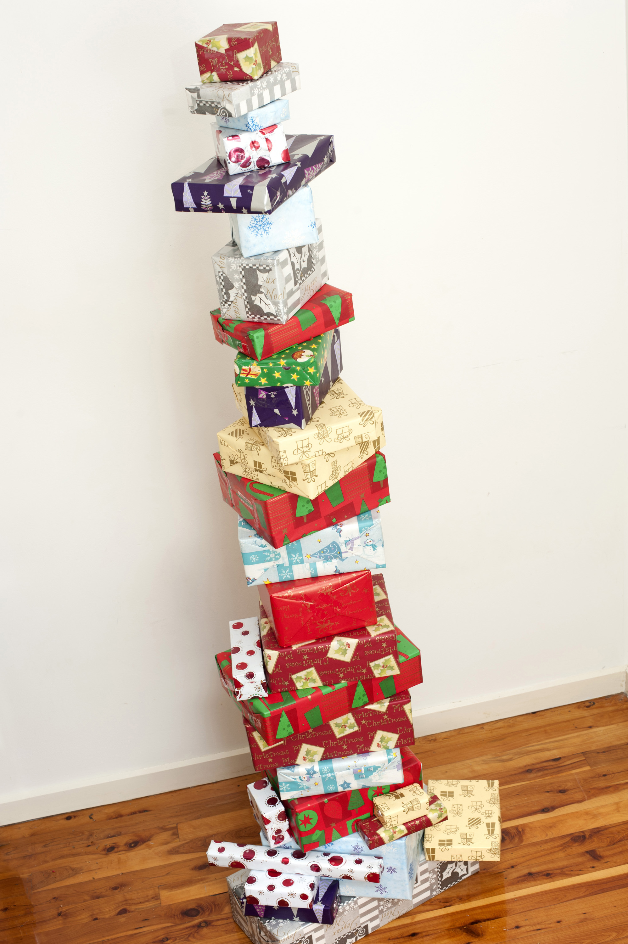 Stacked tower of colourful Christmas gifts neatly balanced one on top of the other in their pretty traditional patterned paper for a unique Xmas decoration in the home