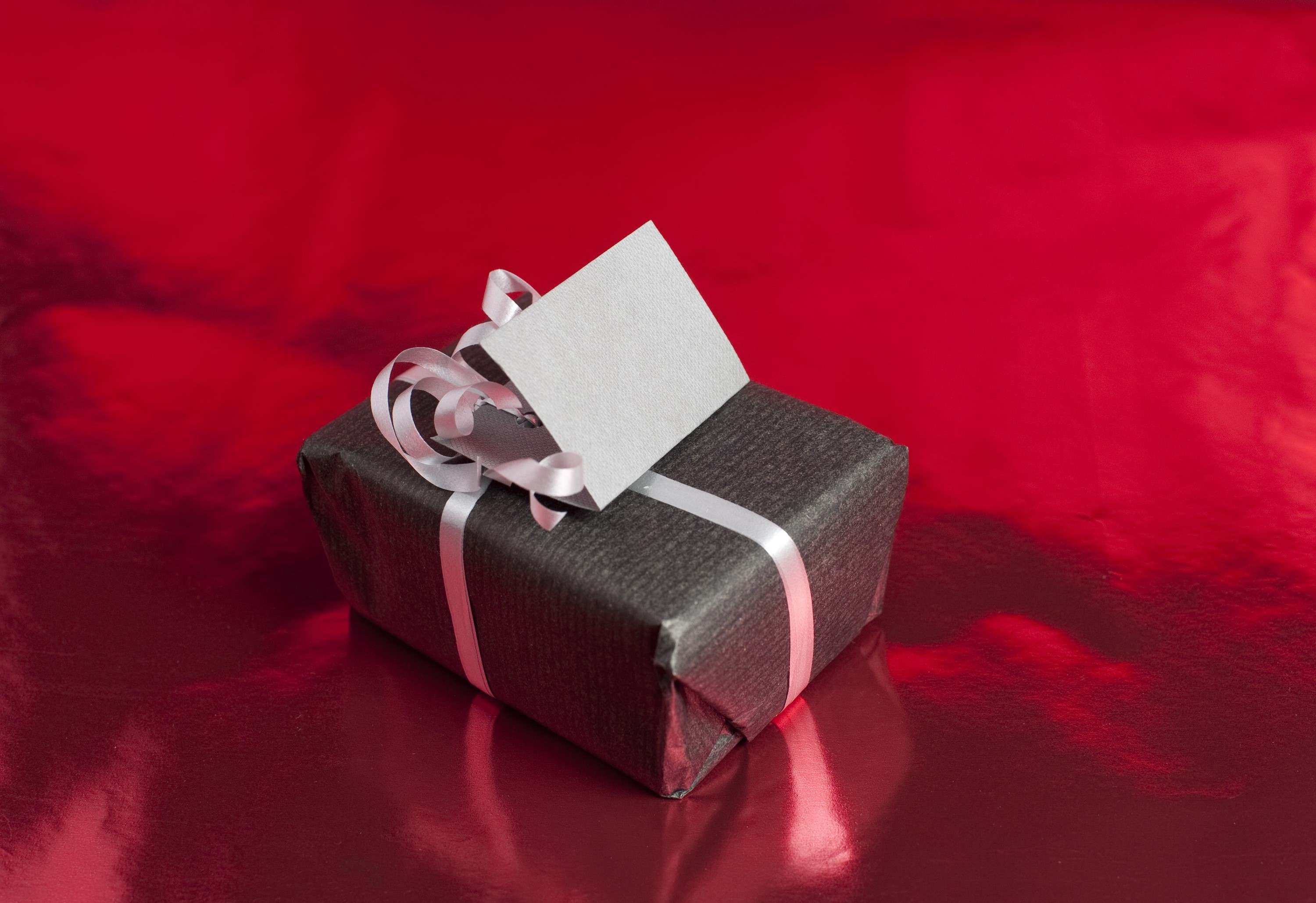 a wrapped christmas gift on a red metallic background