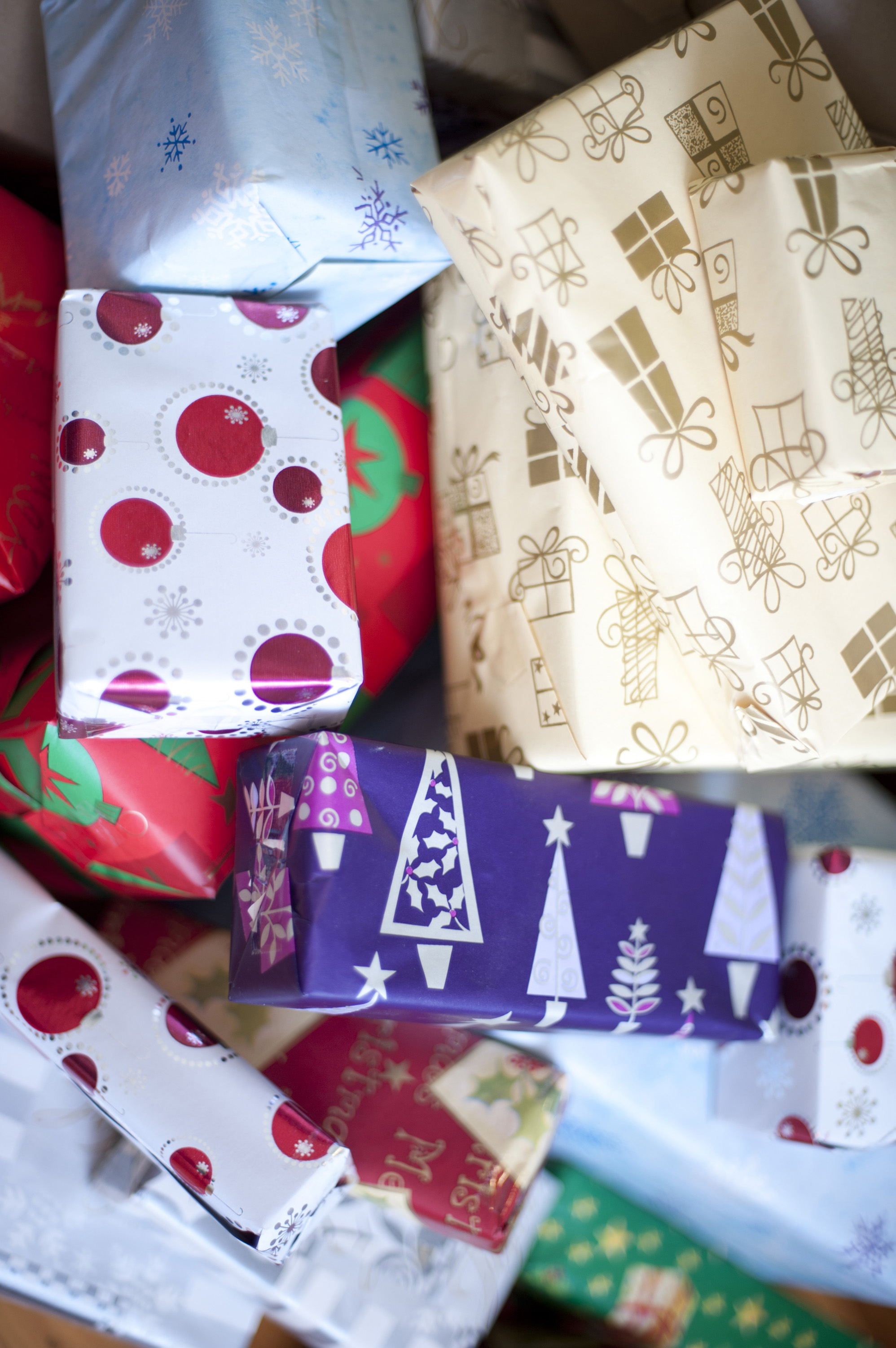 Close-up of Christmas gift boxes wrapped with decorative paper with seasonal patterns