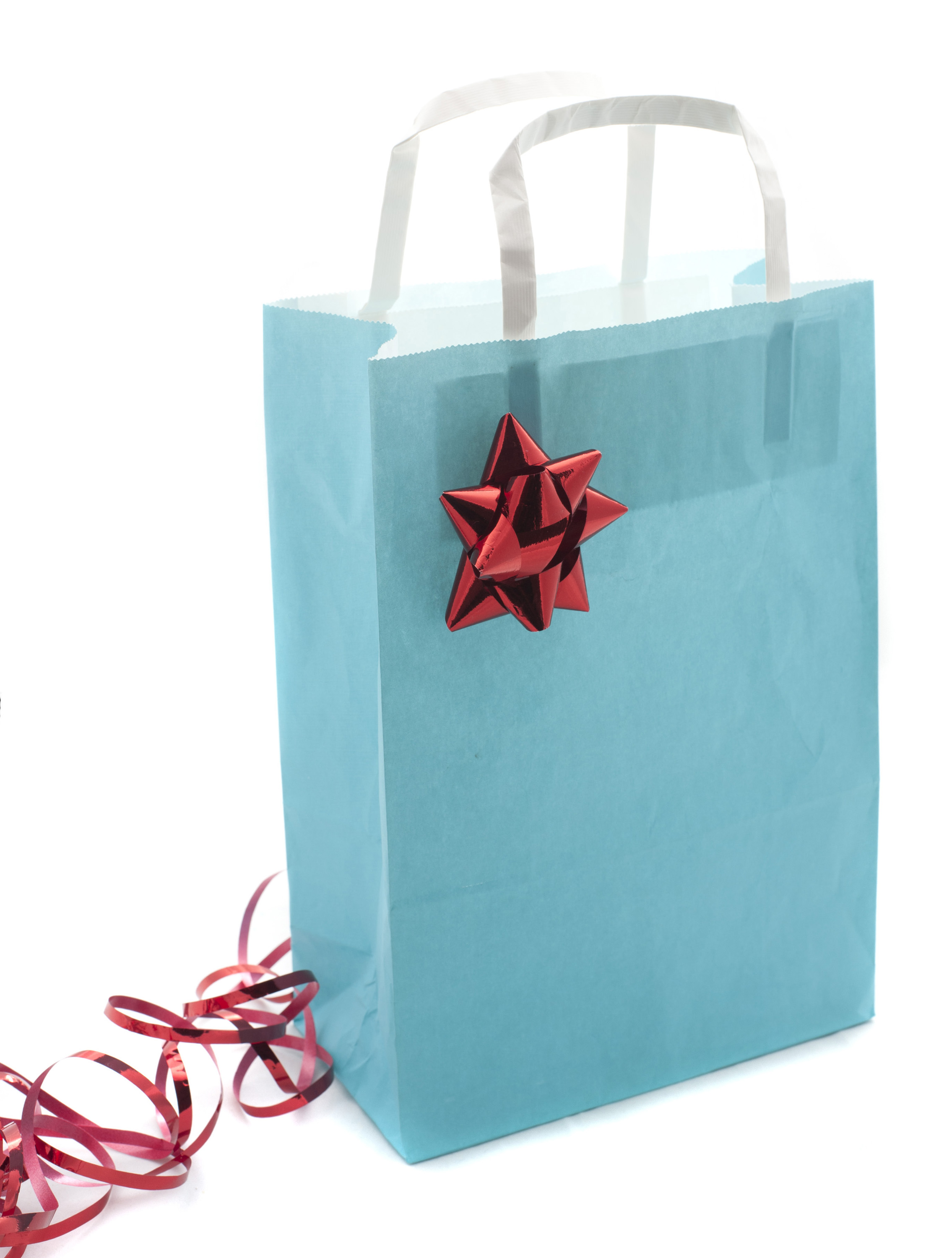 Pretty pastel blue Christmas shopping bag decorated with an ornamental red bow and twirled ribbon on a white background