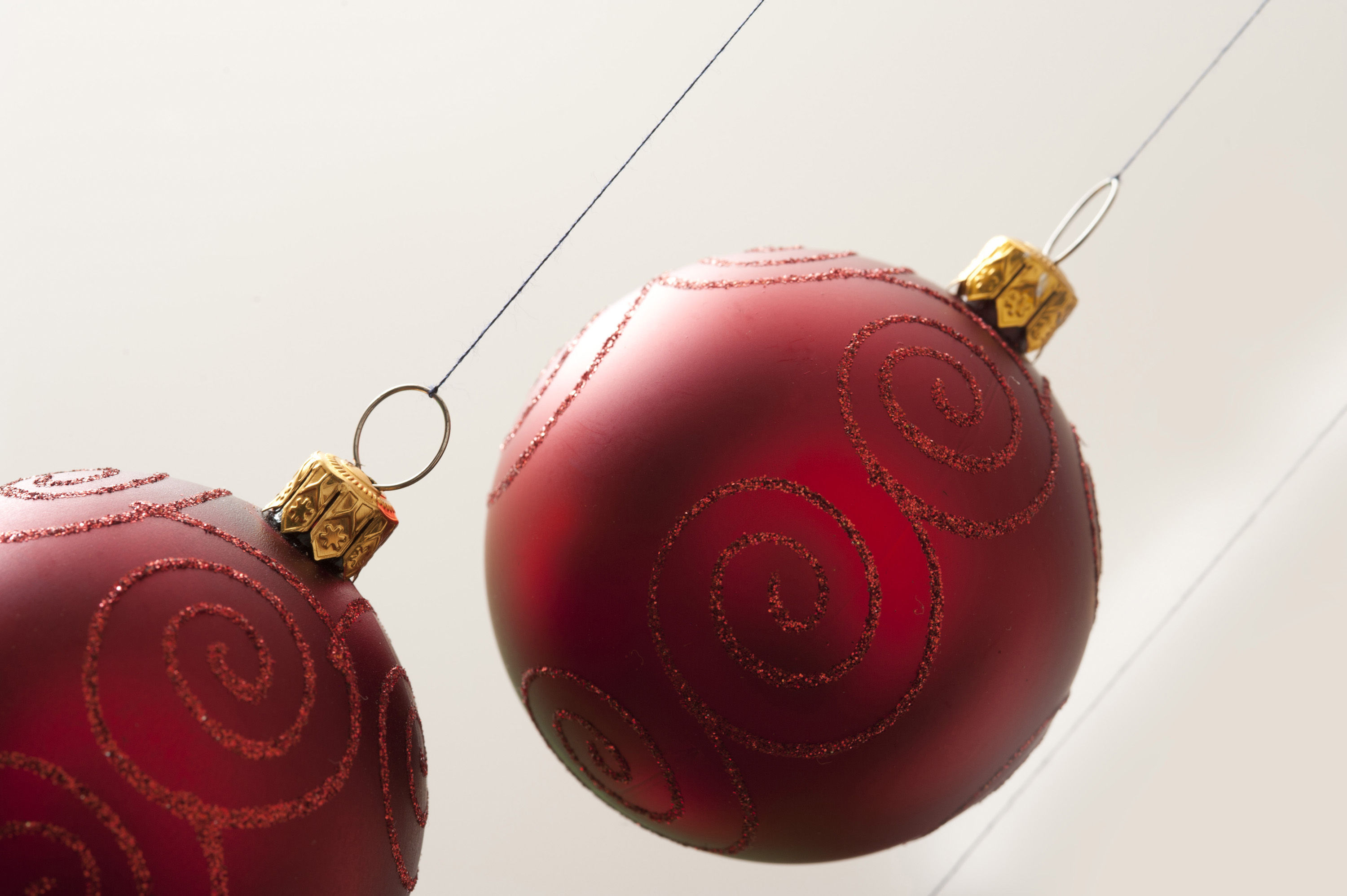 Two red Christmas balls hanging  on white background