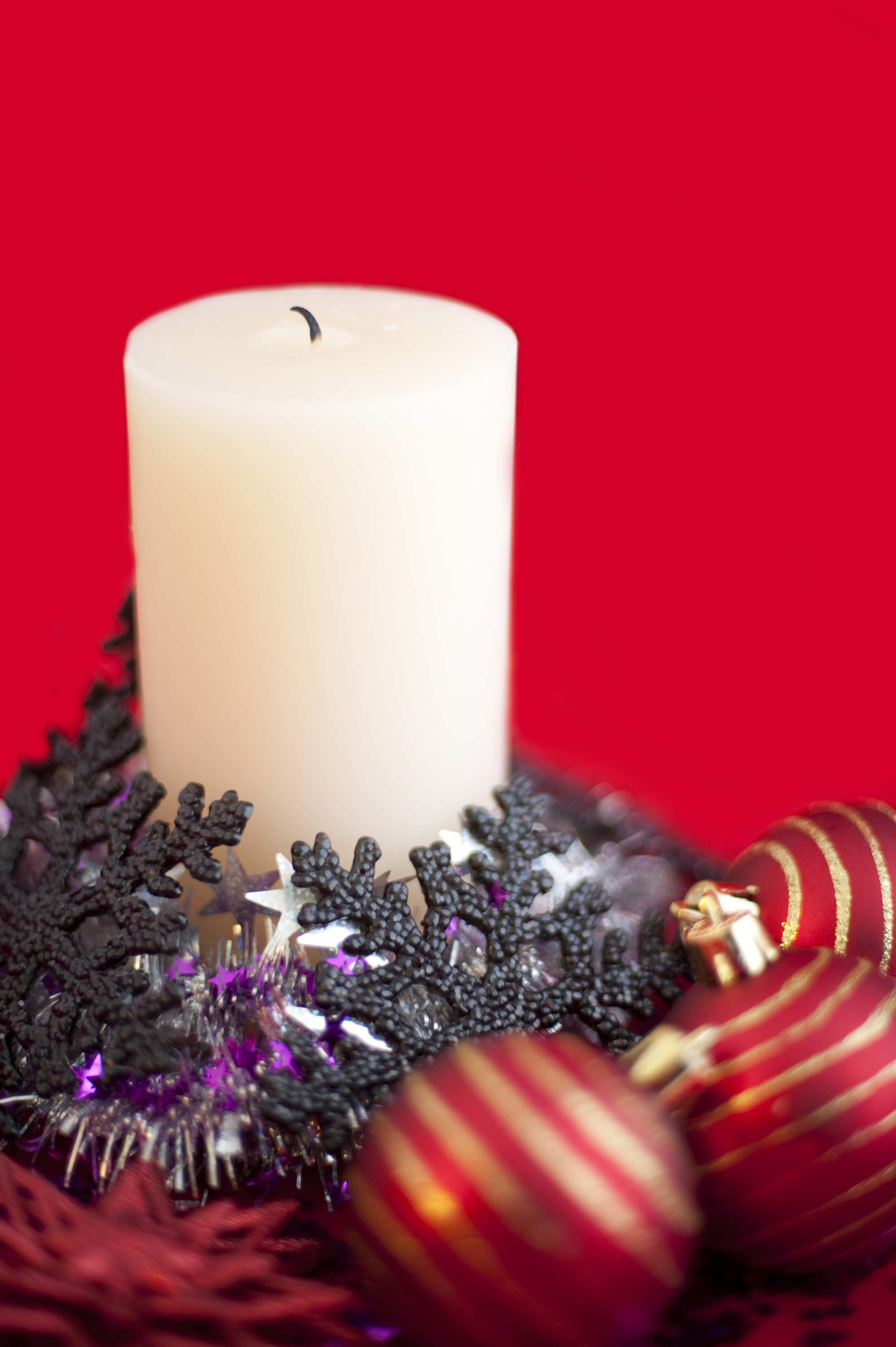 an arrangement of an unlit christmas candle surrounded with various sparkling christmas decorations
