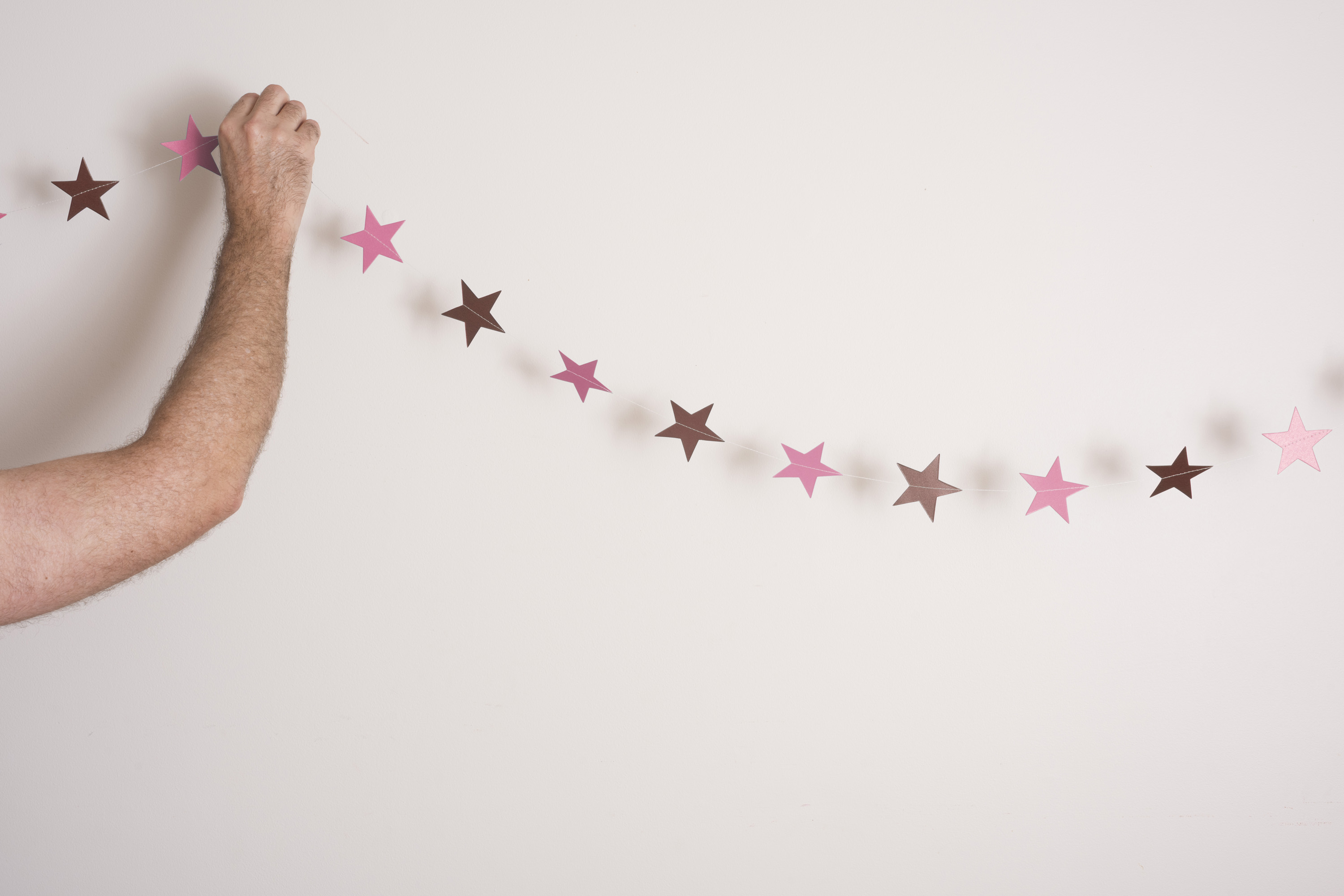 Man hanging a garland of pink and gold Christmas stars or bunting on a white wall with copy space, close up of his arm to the side