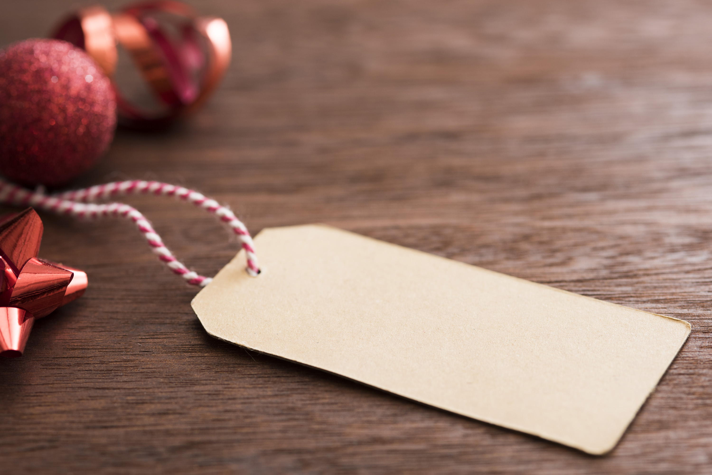 Paper label on a striped string near some red xmas baubles