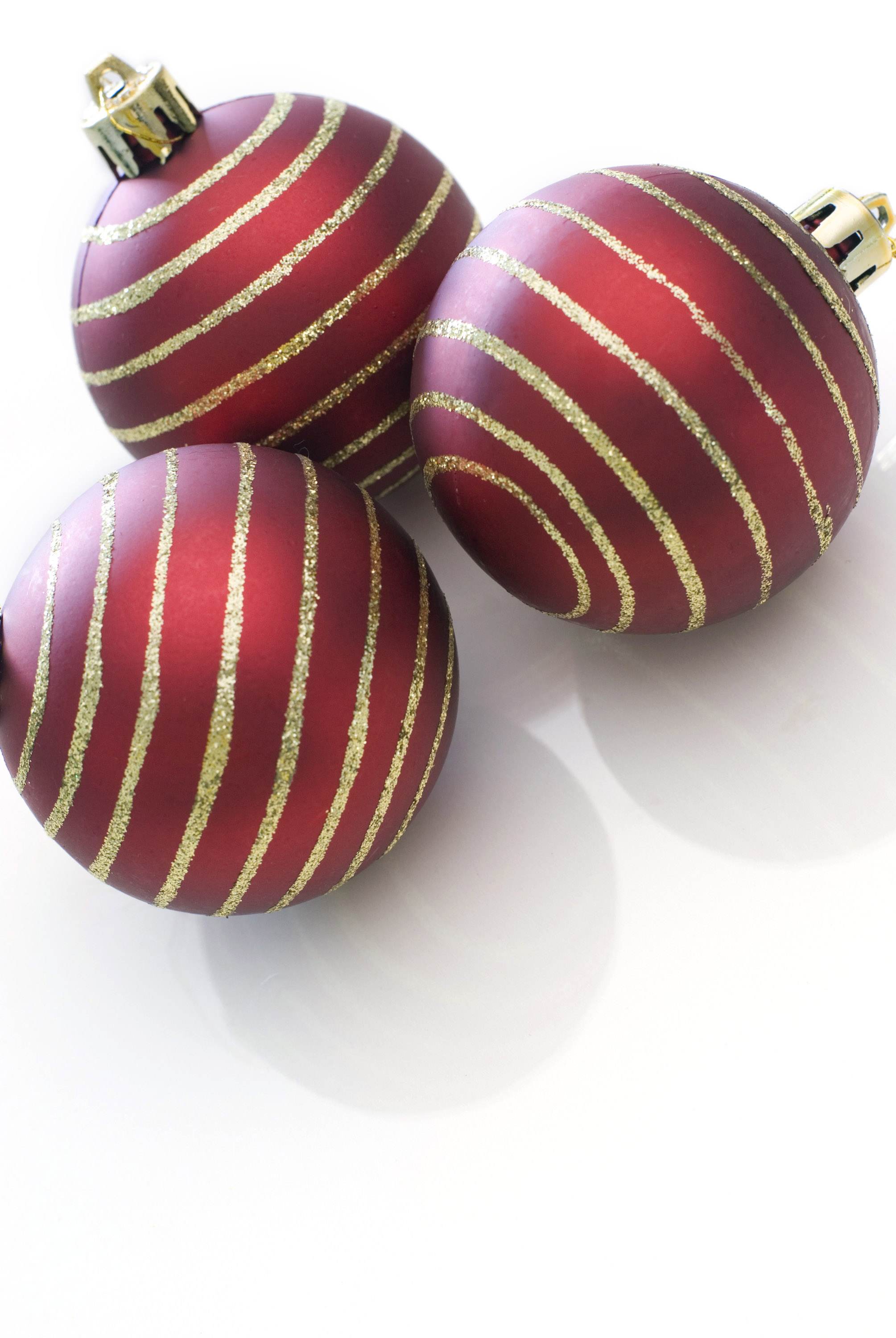 a trio of red christmas tree baubles with gold glitter stripes