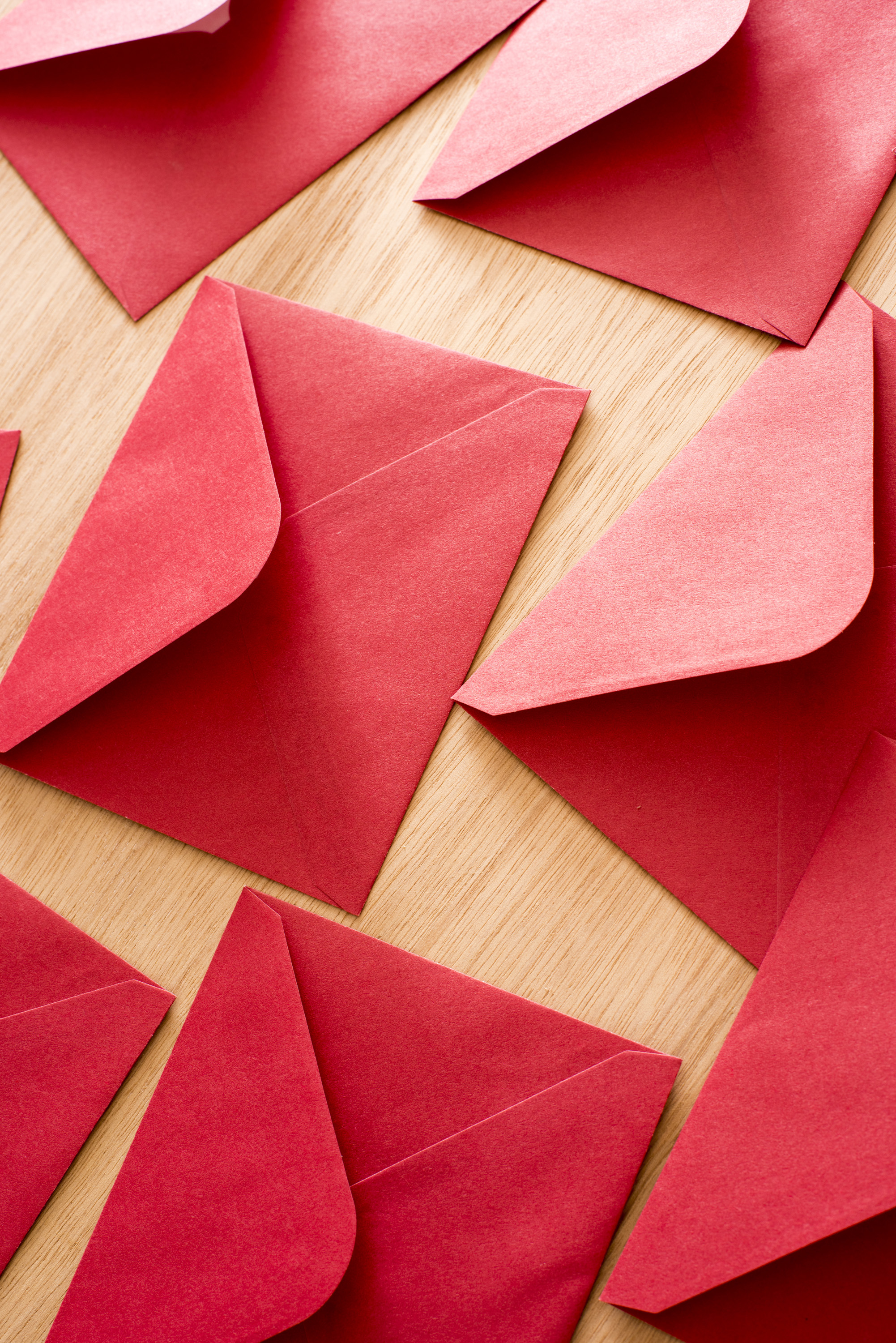 Festive red Christmas or Valentines envelopes lying face down on a wooden table with open flaps in a full frame background